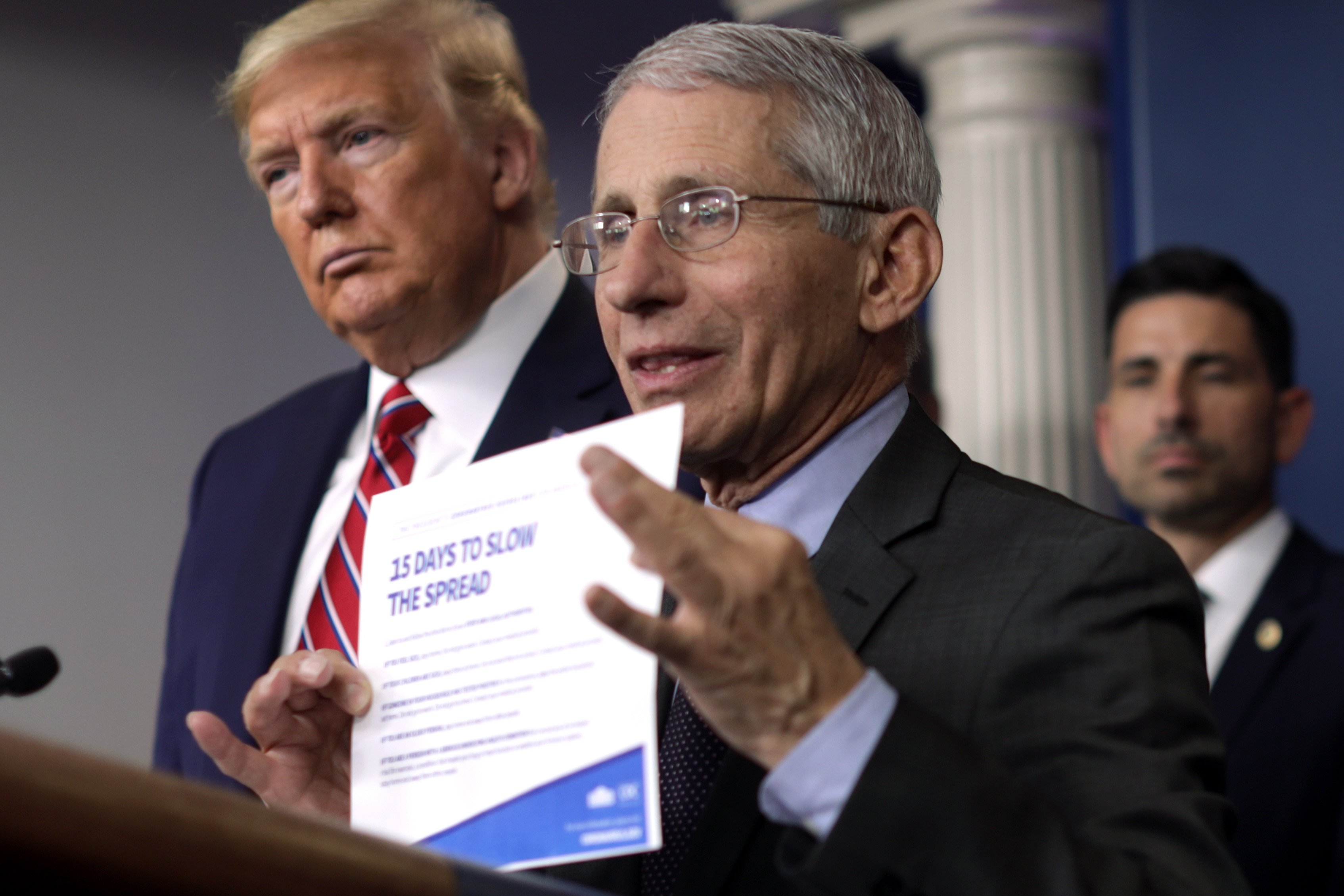 """WASHINGTON, DC - MARCH 20: Director of the National Institute of Allergy and Infectious Diseases Dr. Anthony Fauci holds up the """"15 Days to Slow the Spread"""" instruction as U.S. President Donald Trump looks on during a news briefing on the latest development of the coronavirus outbreak in the U.S. at the James Brady Press Briefing Room at the White House March 20, 2020 in Washington, DC. With deaths caused by the coronavirus rising and foreseeable economic turmoil, the Senate is working on legislation for a $1 trillion aid package to deal with the COVID-19 pandemic. President Trump announced that tax day will be delayed from April 15 to July 15. (Photo by Alex Wong/Getty Images)"""