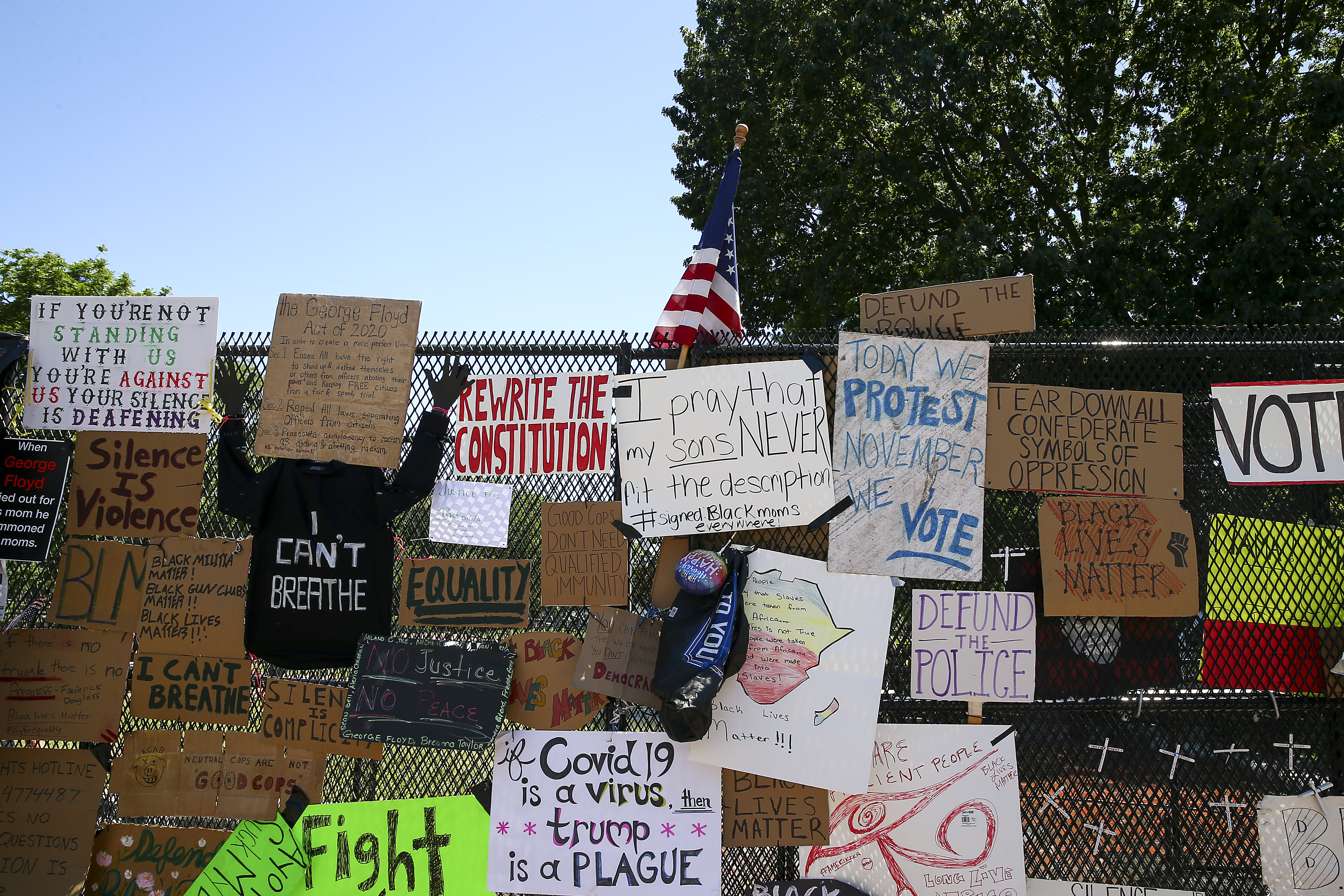 """WASHINGTON, DC - JUNE 08: The steel fence at Lafayette Park has become a makeshift memorial at 16th street after """"Defund The Police"""" was painted on the street near the White House on June 08, 2020 in Washington, DC. (Photo by Tasos Katopodis/Getty Images)"""
