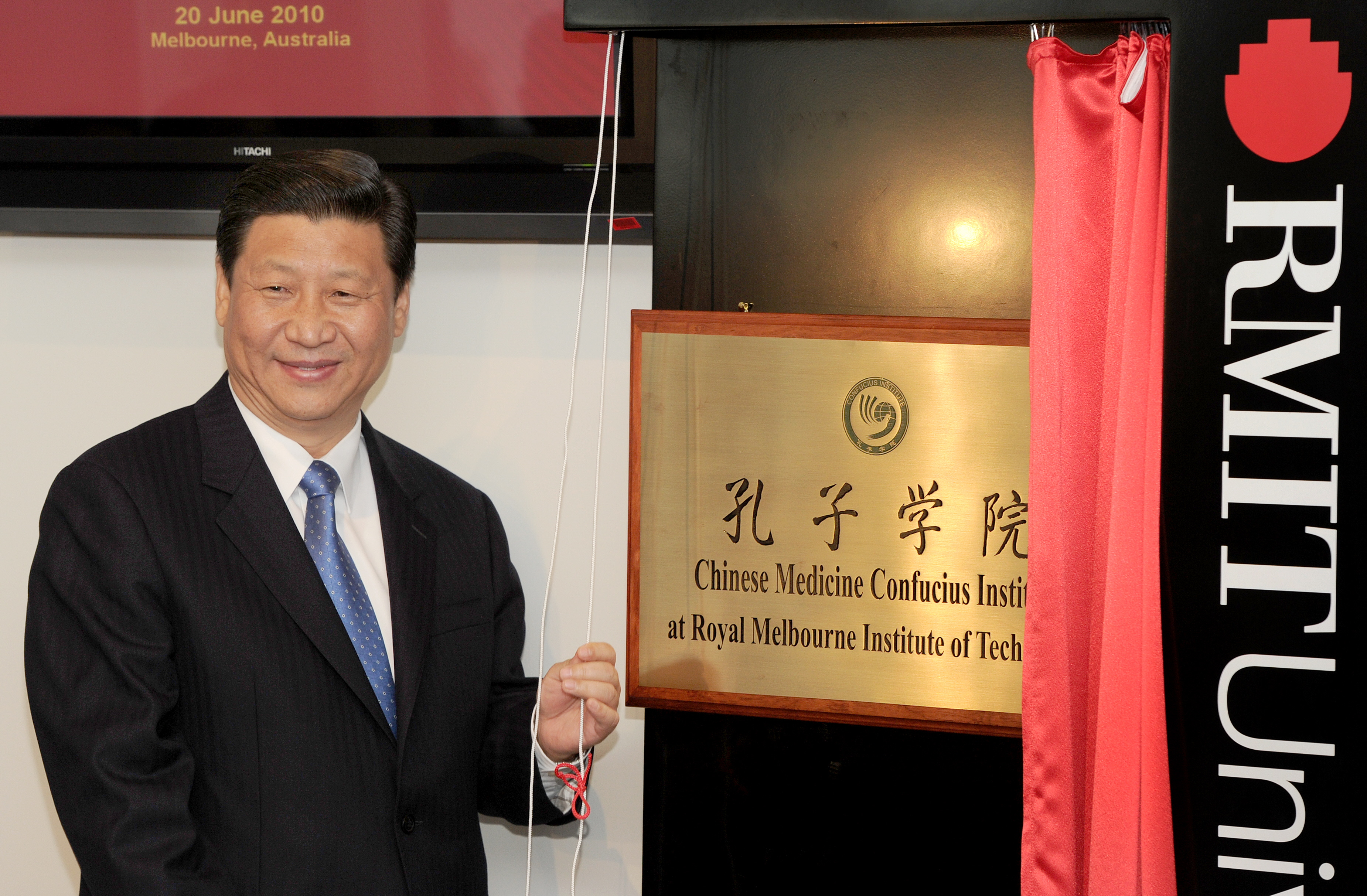 China's Vice President Xi Jinping unveils the plaque at the opening of Australia's first Chinese Medicine Confucius Institute at the RMIT University in Melbourne on June 20, 2010. The Confucius Institute will promote the study of Chinese culture and language with a focus on Chinese Medicine - one of the world's oldest and longest standing healthcare systems, tracing back more than 2,500 years. Xi is on a five-day visit to Australia. AFP PHOTO/William WEST (Photo credit should read WILLIAM WEST/AFP via Getty Images)