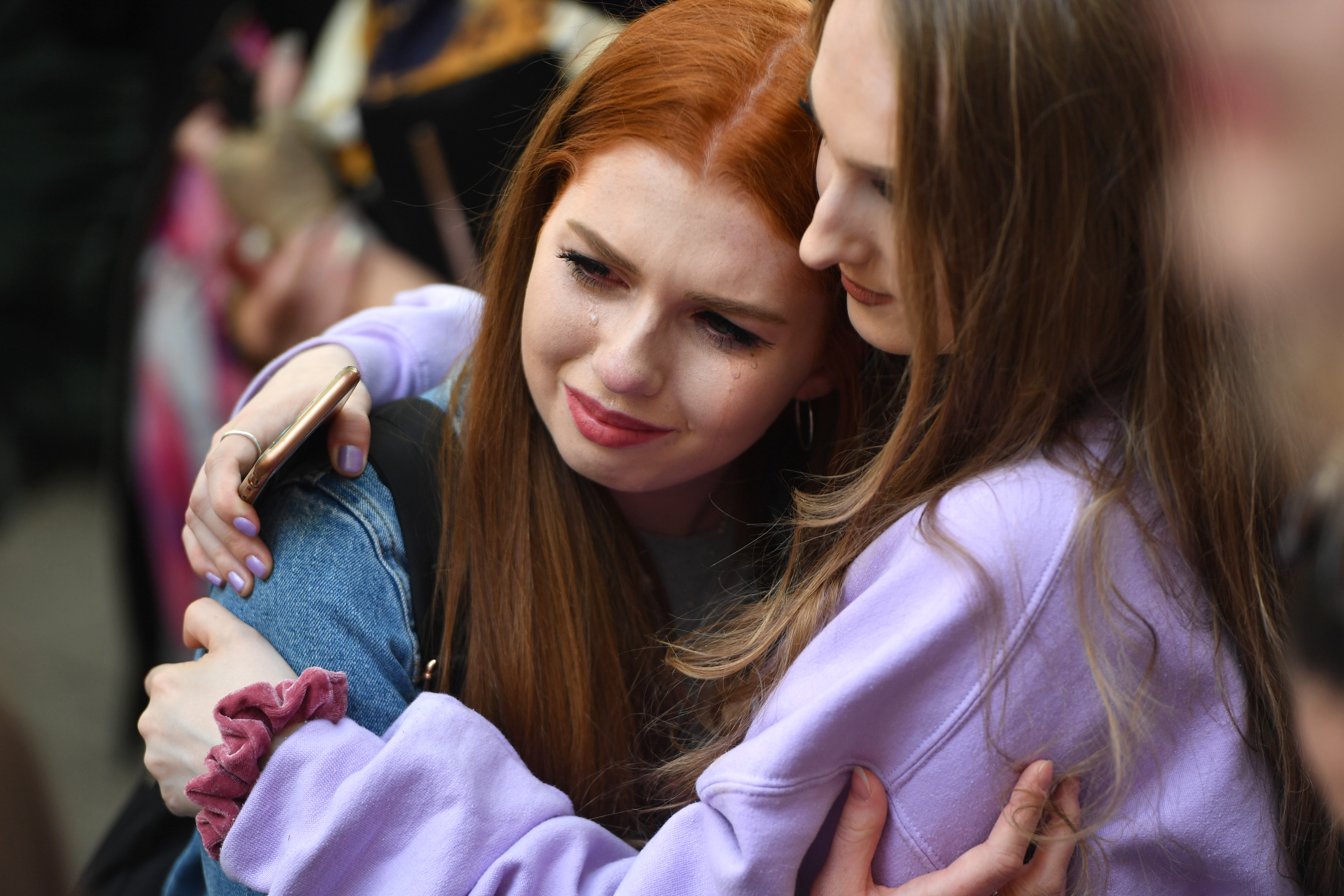 MANCHESTER, ENGLAND - MAY 22: Members of the public reacts as the Manchester Survivors Choir perform following a two minute silence in memory of the victims of the Manchester Bombing in Saint Anne's Square on May 22, 2019 in Manchester, England. The suicide bomb attack took place following a concert at Manchester Arena by US singer Ariana Grande and claimed the lives of 22 people. (Photo by Anthony Devlin/Getty Images)