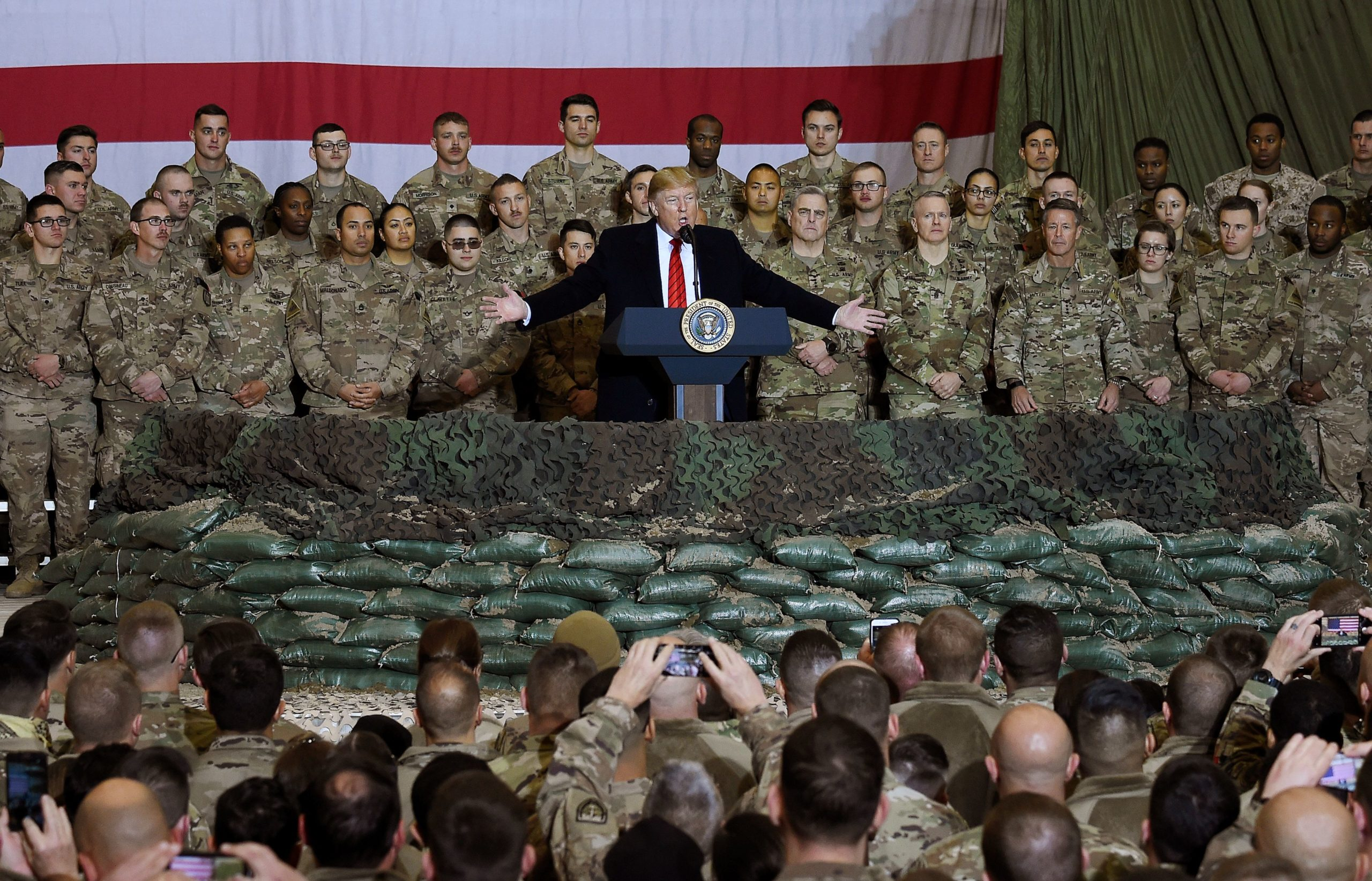 In this file photo taken on November 28, 2019, US President Donald Trump speaks to the troops during a surprise Thanksgiving day visit at Bagram Air Field in Afghanistan. (Olivier Douliery/AFP via Getty Images)