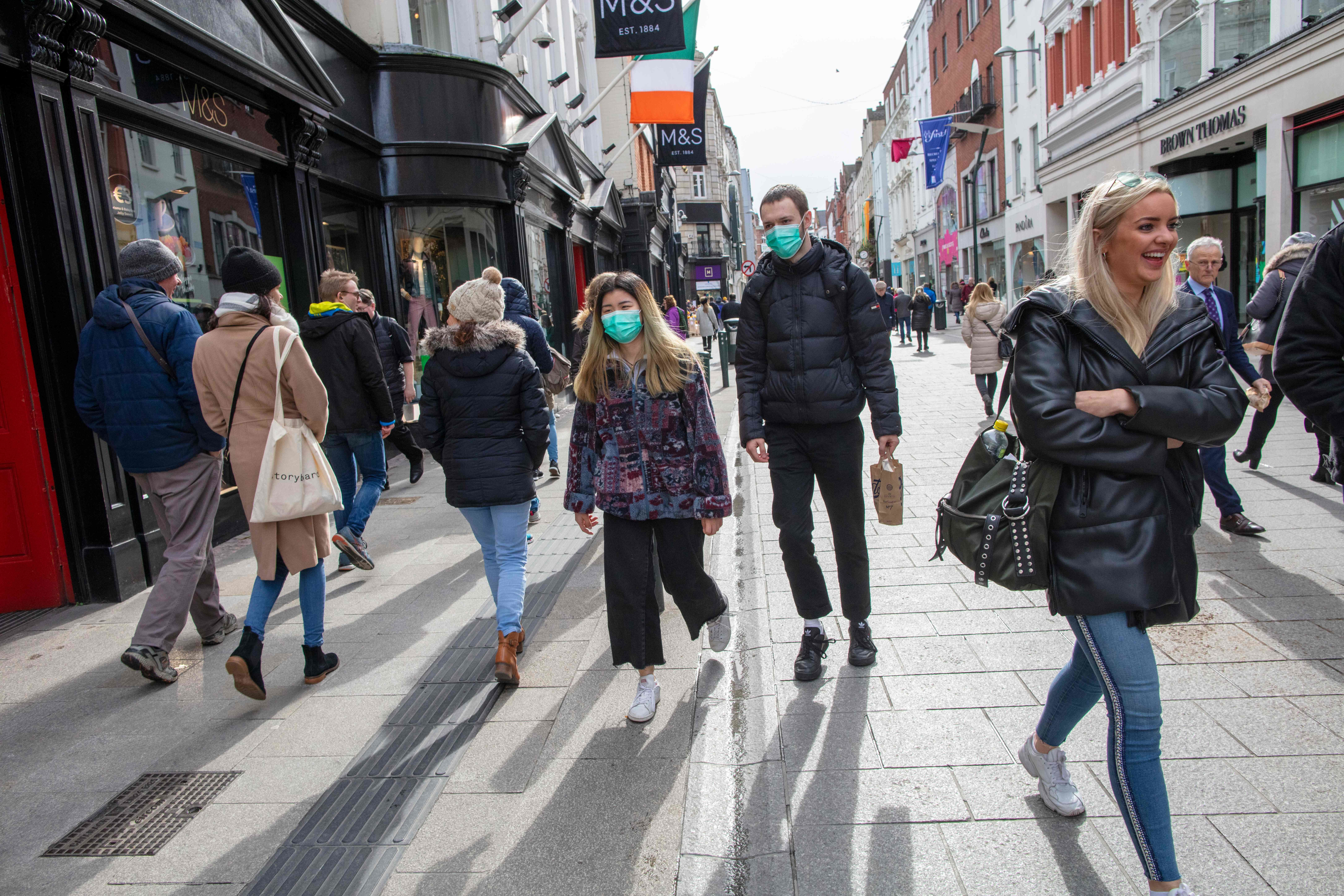 A couple wear surgical masks while shopping in the Grafton shopping area of in Dublin, Ireland on March 12, 2020. (Paul Faith/AFP via Getty Images)