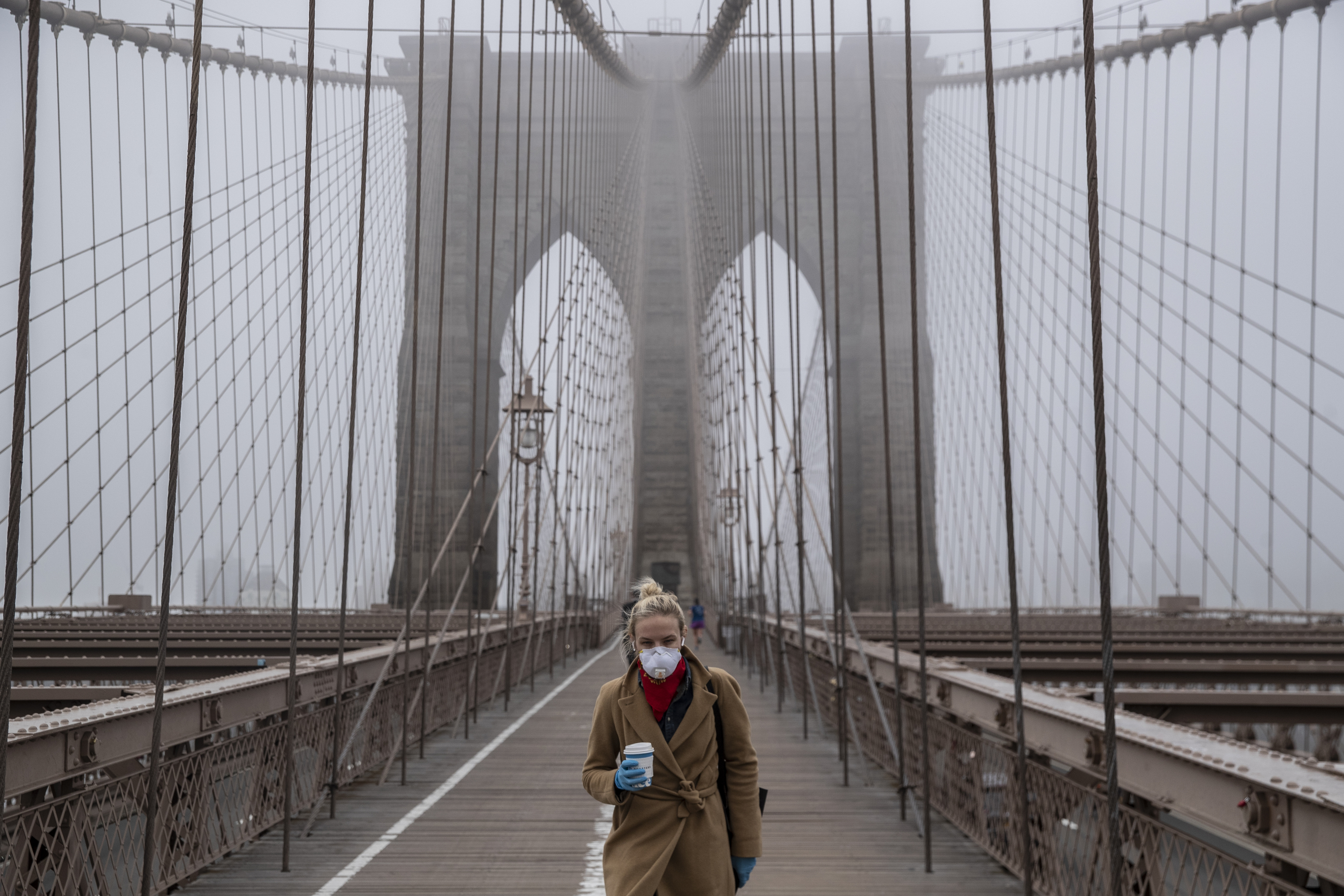 NEW YORK, NY - MARCH 20: A woman wearing a mask walks the Brooklyn Bridge in the midst of the coronavirus (COVID-19) outbreak on March 20, 2020 in New York City. The economic situation in the city continued to decline as New York Gov Andrew Cuomo ordered all nonessential businesses to keep all their workers at home and New York weighed a shelter in place order for the entire city. (Photo by Victor J. Blue/Getty Images)