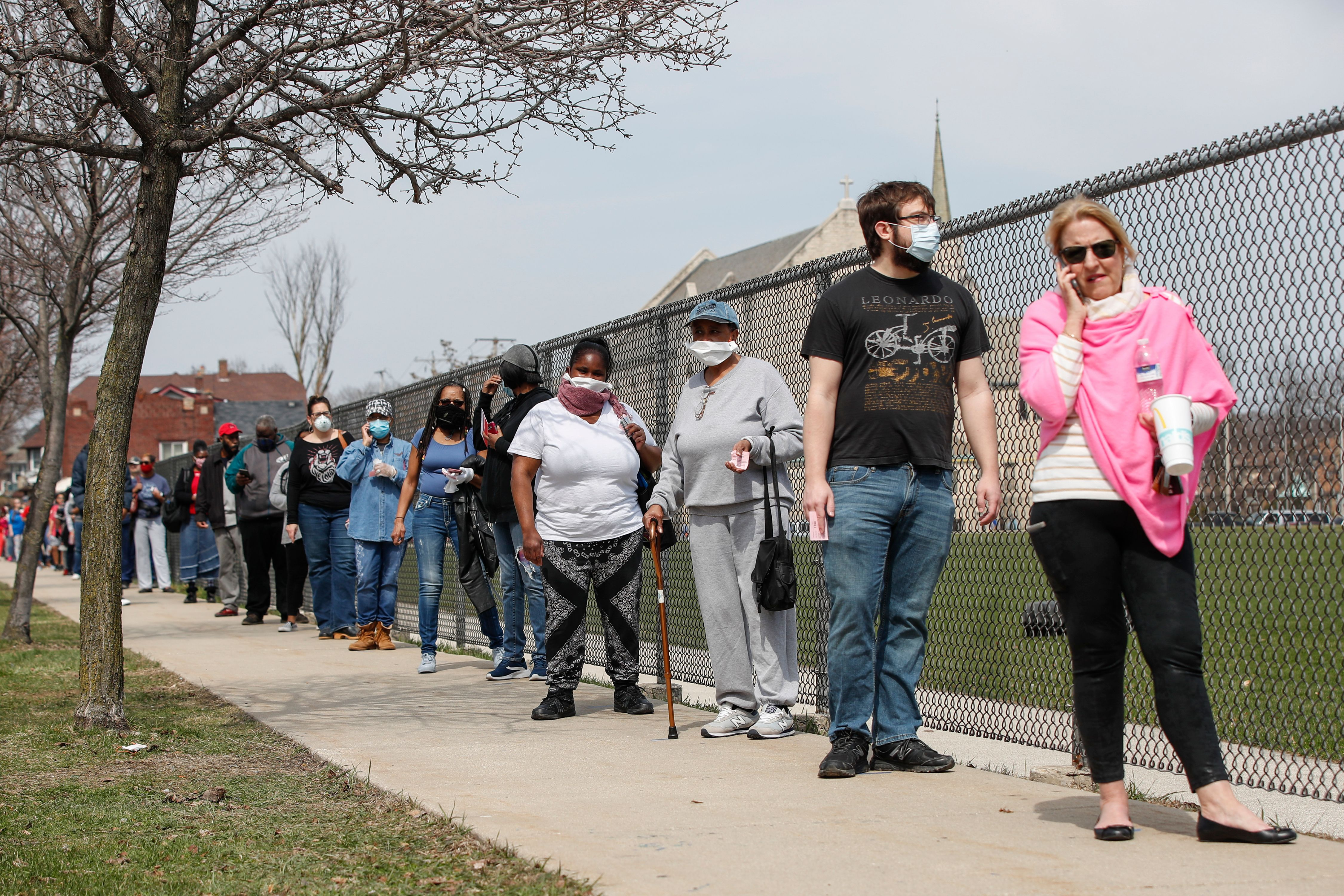 Residents wait in long line to vote in a presidential primary election outside the Riverside High School in Milwaukee, Wisconsin, on April 7, 2020. (KAMIL KRZACZYNSKI/AFP via Getty Images)