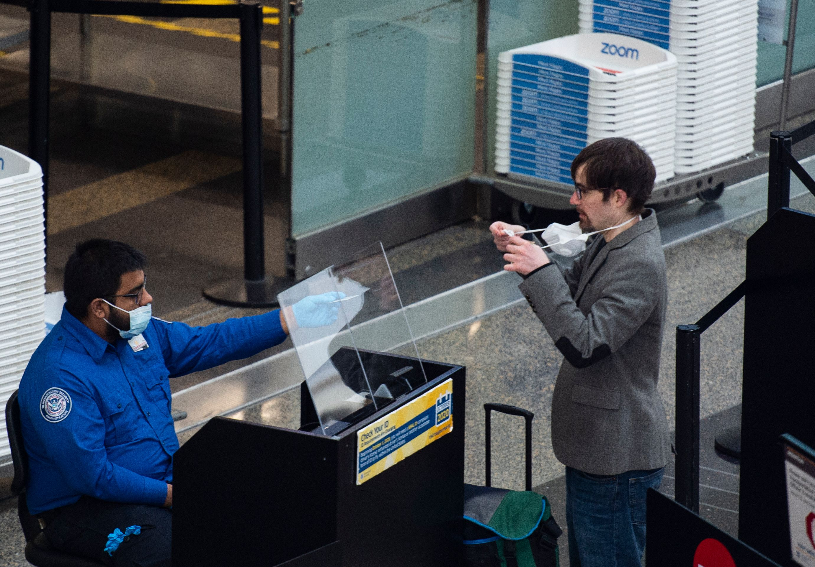 A passenger removes his mask as he has his ID checked by a Transportation Security Administration (TSA) employee in Ronald Reagan Washington National Airport in Arlington, Virginia, on May 12, 2020. - (Photo by ANDREW CABALLERO-REYNOLDS/AFP via Getty Images)