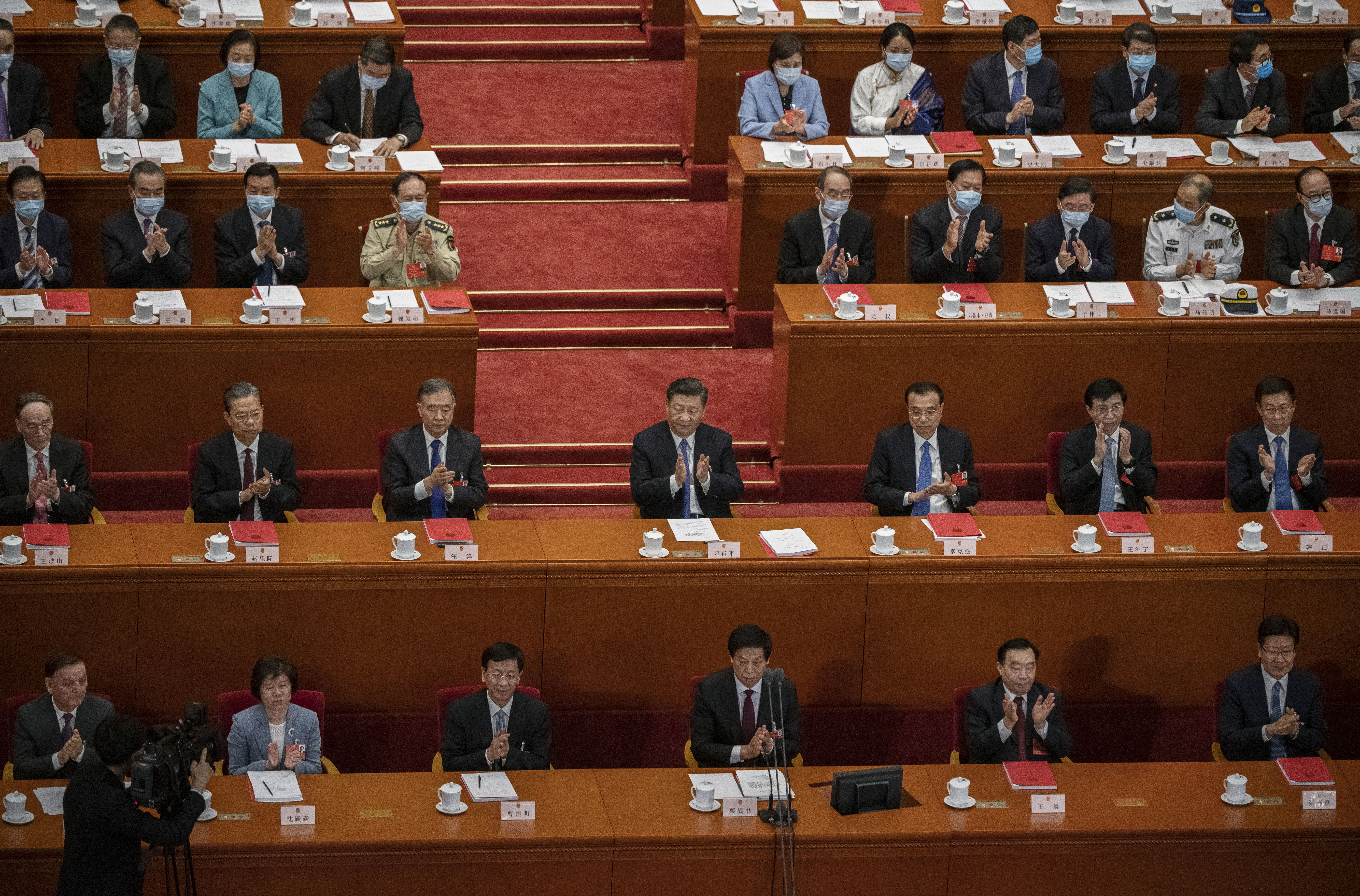 Chinese president Xi Jinping, center, and other members of the Chinese government applaud during the closing session of the National People's Congress at the Great Hall of the People in May in Beijing, China. (Kevin Frayer/Getty Images)