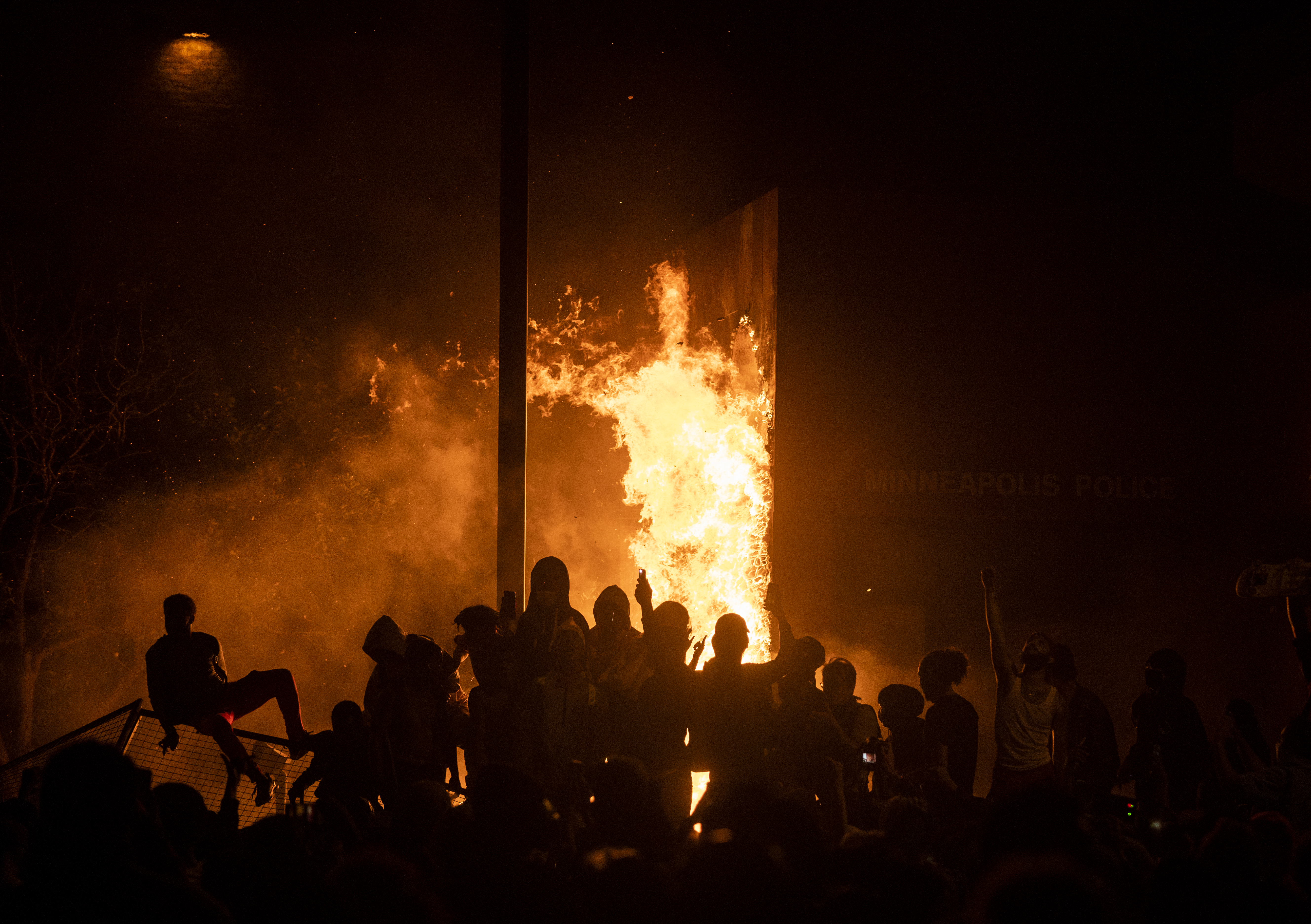 MINNEAPOLIS, MN - MAY 28: Protesters cheer as the Third Police Precinct burns behind them on May 28, 2020 in Minneapolis, Minnesota. As unrest continues after the death of George Floyd police abandoned the precinct building, allowing protesters to set fire to it. (Photo by Stephen Maturen/Getty Images)