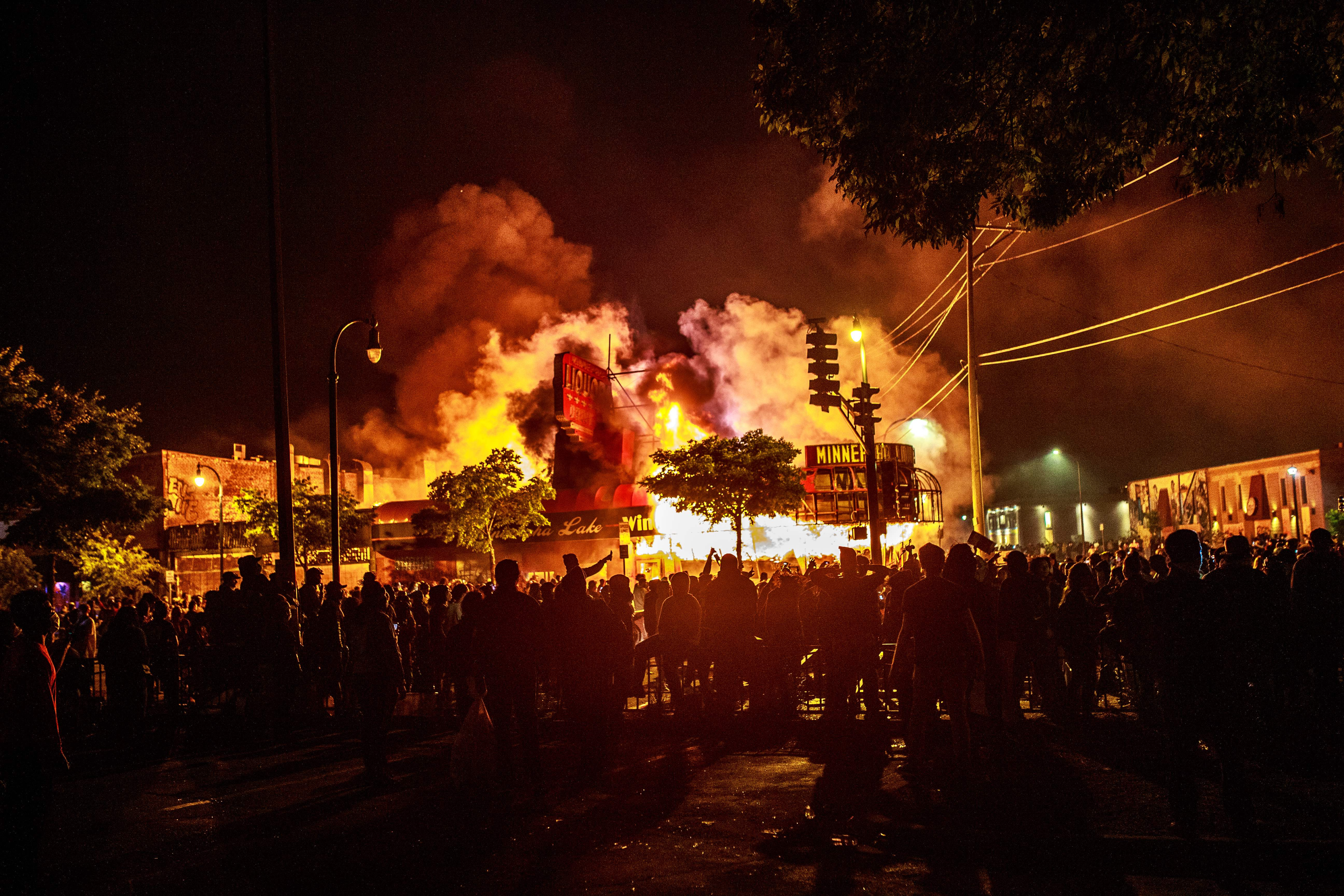 Protesters gather around a liquor store in flames near the Third Police Precinct on May 28, 2020 in Minneapolis, Minnesota, during a protest over the death of George Floyd, an unarmed black man, who died after a police officer kneeled on his neck for several minutes. - A police precinct in Minnesota went up in flames late on May 28 in a third day of demonstrations as the so-called Twin Cities of Minneapolis and St. Paul seethed over the shocking police killing of a handcuffed black man. The precinct, which police had abandoned, burned after a group of protesters pushed through barriers around the building, breaking windows and chanting slogans. A much larger crowd demonstrated as the building went up in flames. (Photo by Kerem Yucel/AFP via Getty Images)