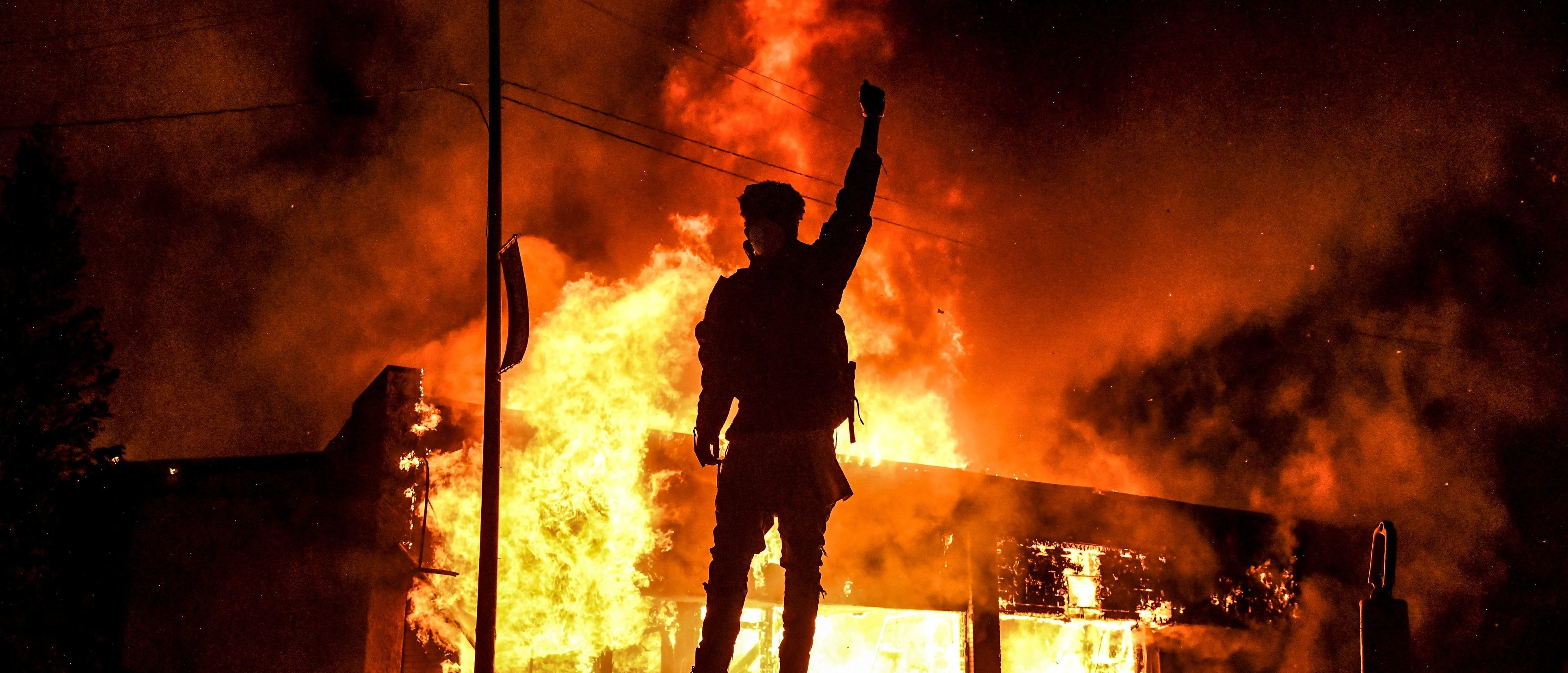 A protester reacts standing in front of a burning building set on fire during a demonstration in Minneapolis, Minnesota, on May 29, 2020, over the death of George Floyd, a black man who died after a white policeman kneeled on his neck for several minutes. (CHANDAN KHANNA/AFP via Getty Images)