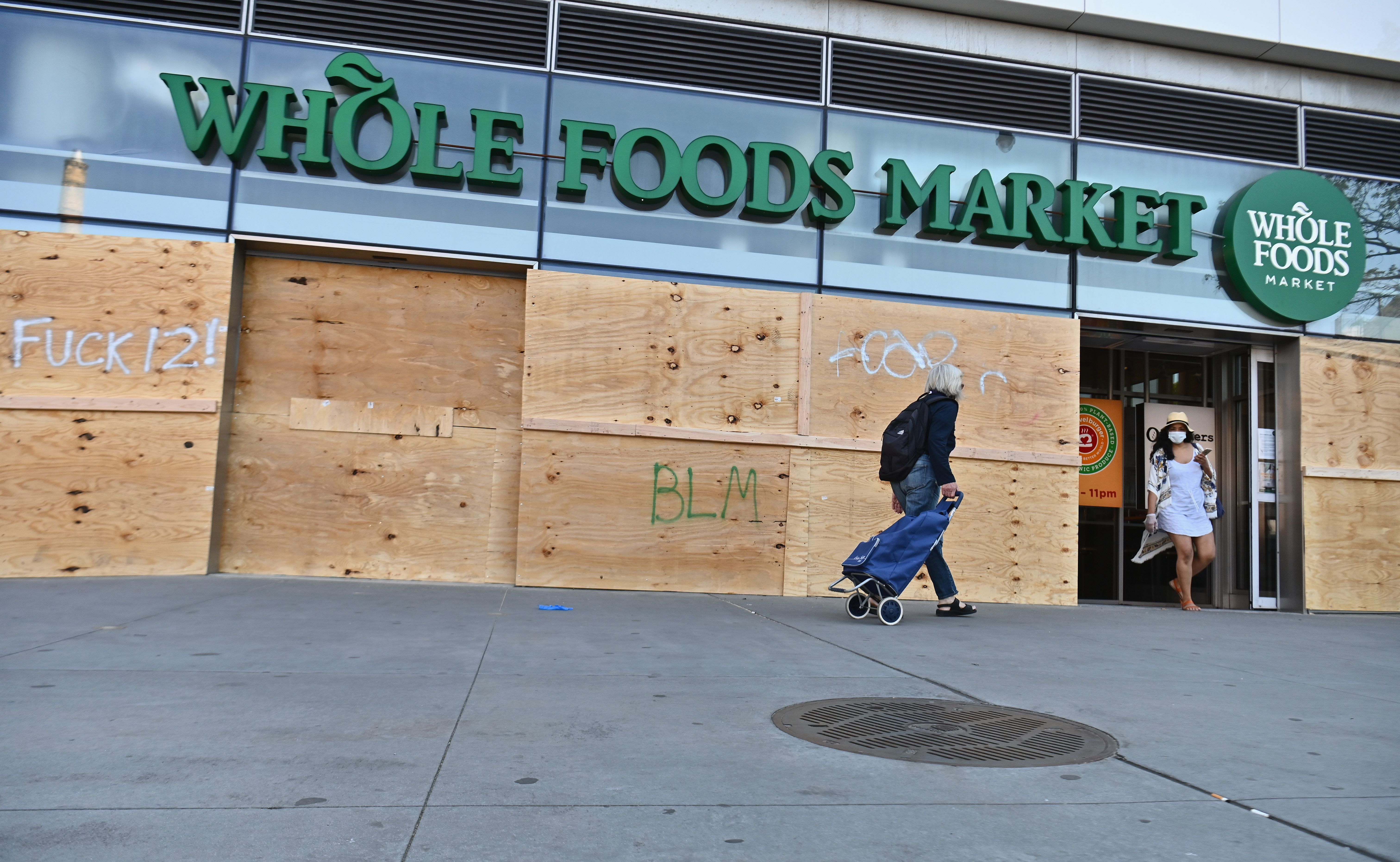 People go shopping at a Brooklyn, New York Whole Foods Market store, which is boarded up on June 1 after a night of protest over the death of George Floyd. (Angela Weiss/AFP via Getty Images)