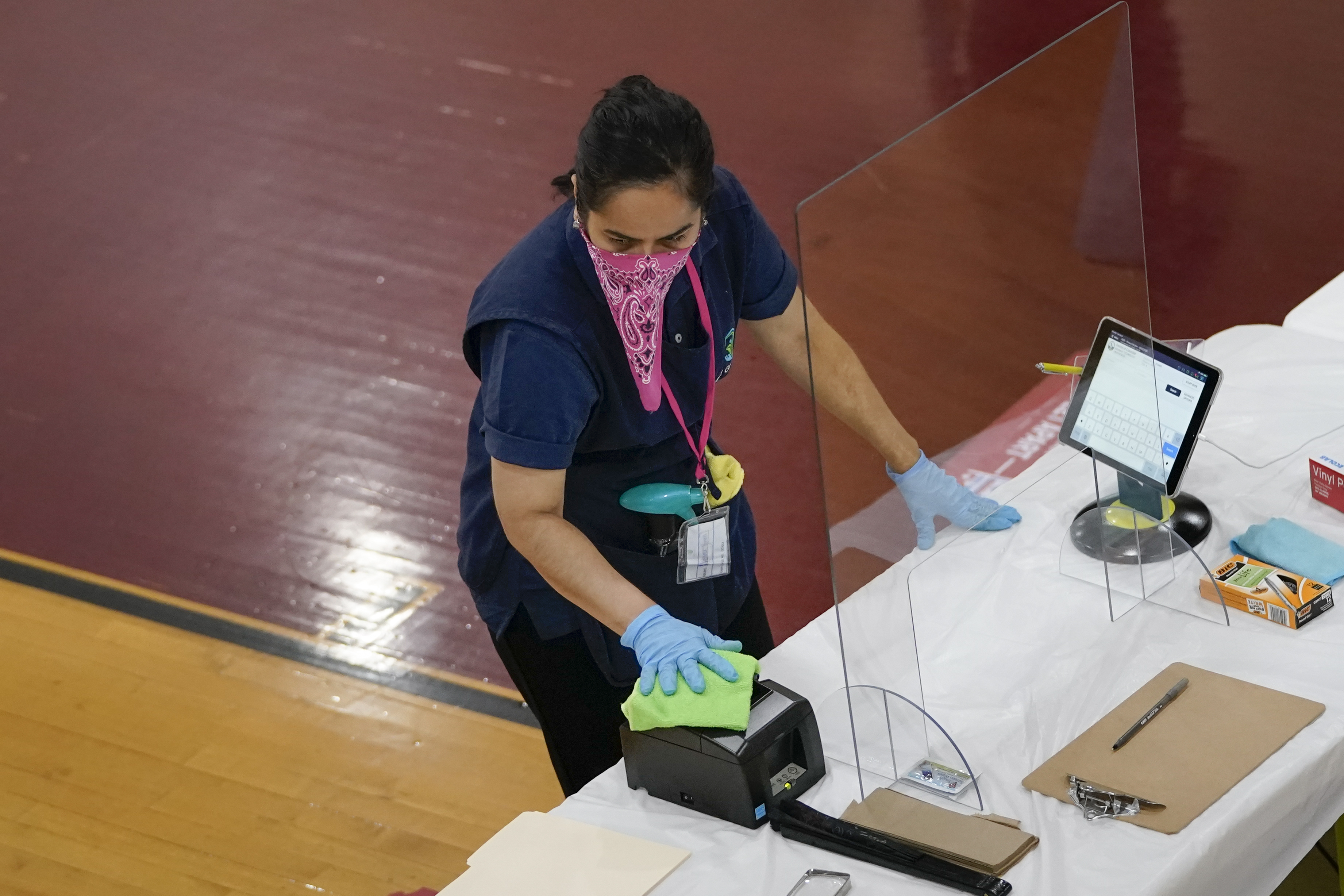 A worker cleans a check-in station at McKinley Technology High School on primary election day on June 2, 2020 in Washington, DC.