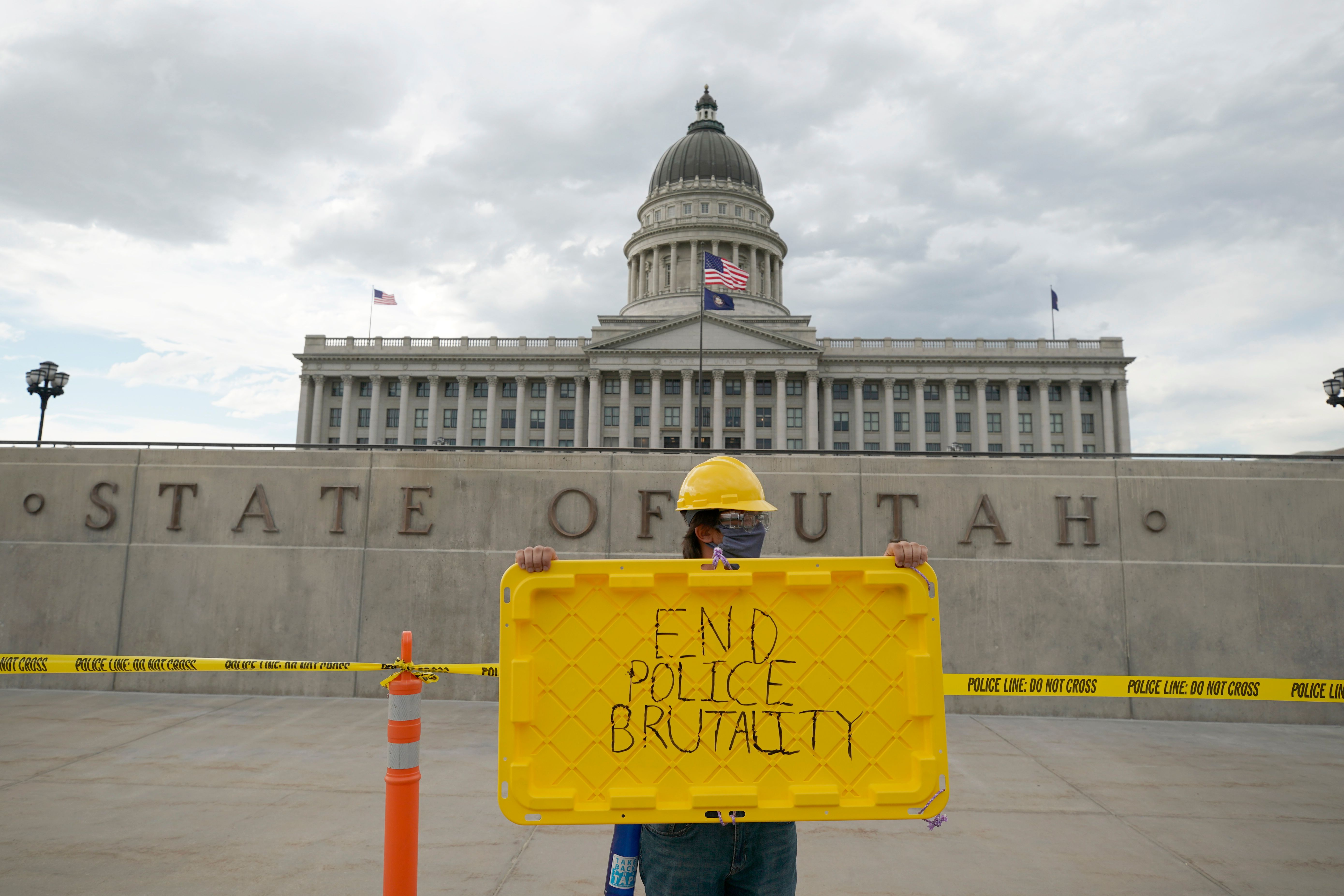 A protester holds a sign in front of the Utah State Capitol building during a protest in Salt Lake City, Utah on June 5, 2020. (Photo by GEORGE FREY/AFP via Getty Images)