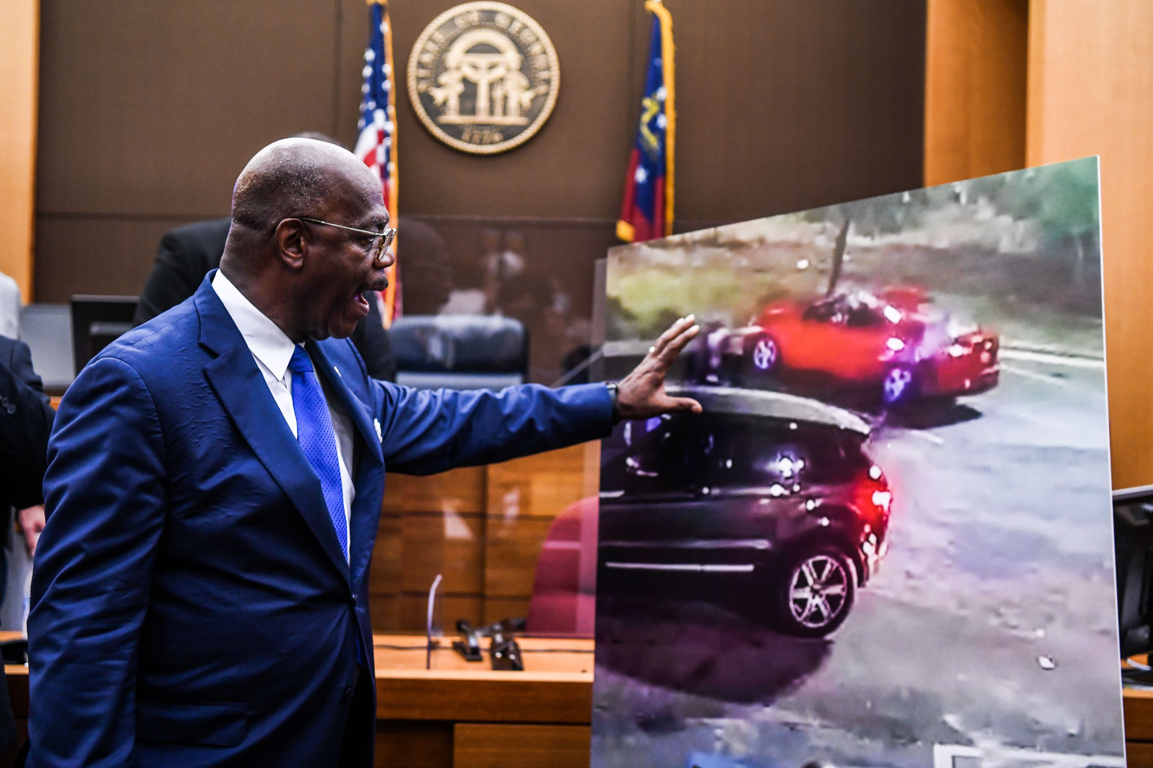 Fulton County District Attorney Paul Howard shows a picture of the incident in a courtroom as he announces 11 charges against former Atlanta Police Officer Garrett Rolfe on June 17, 2020, in Atlanta, Georgia. (Photo by CHANDAN KHANNA/AFP via Getty Images)