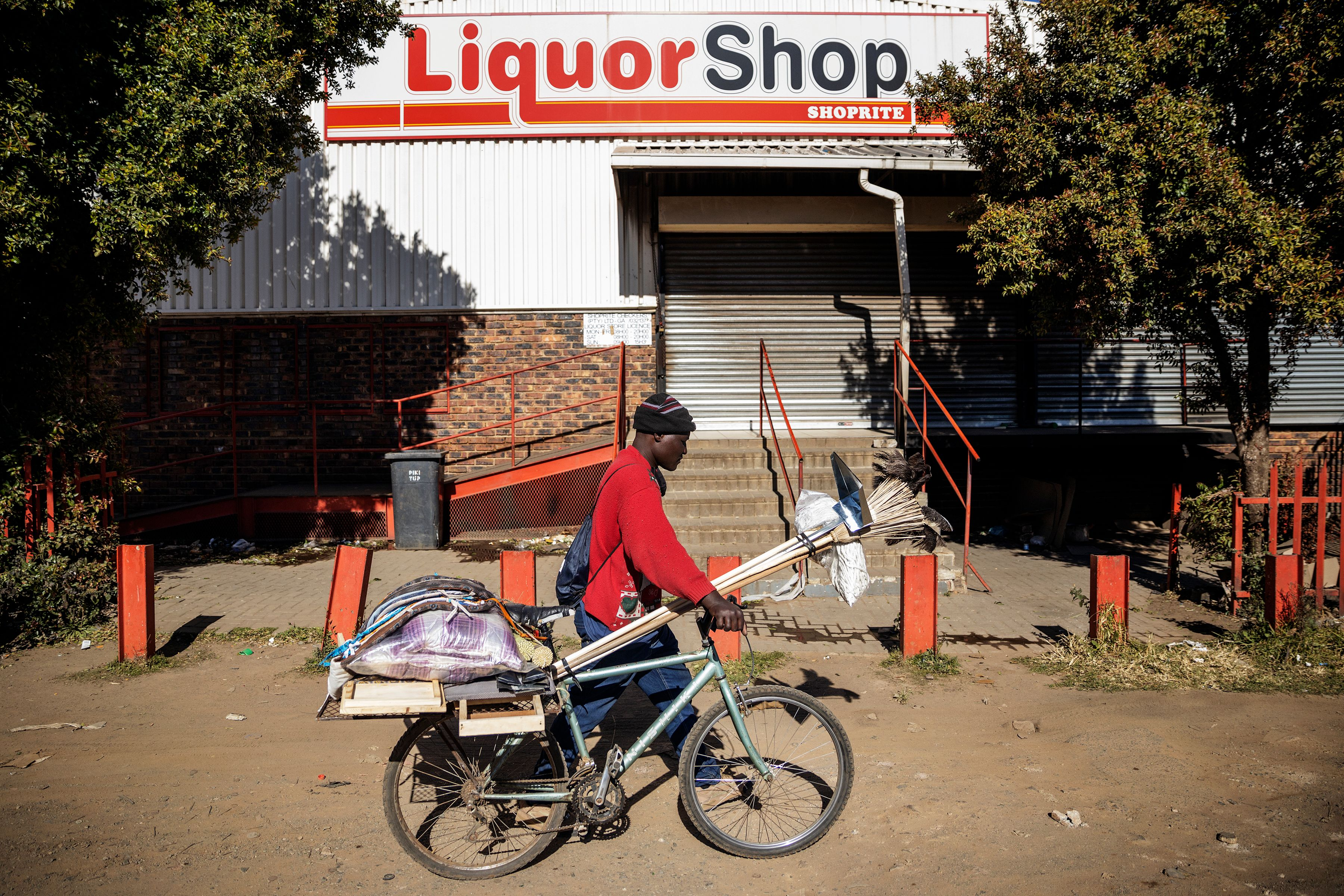 A man walks past a closed liquor shop in Soweto, on July 13, 2020. - South African President Cyril Ramaphosa on July 12, 2020 re-imposed a night curfew and suspended alcohol sales as COVID-19 coronavirus infections spiked and the health system risked being overwhelmed. (Photo by Michele Spatari / AFP) (Photo by MICHELE SPATARI/AFP via Getty Images)