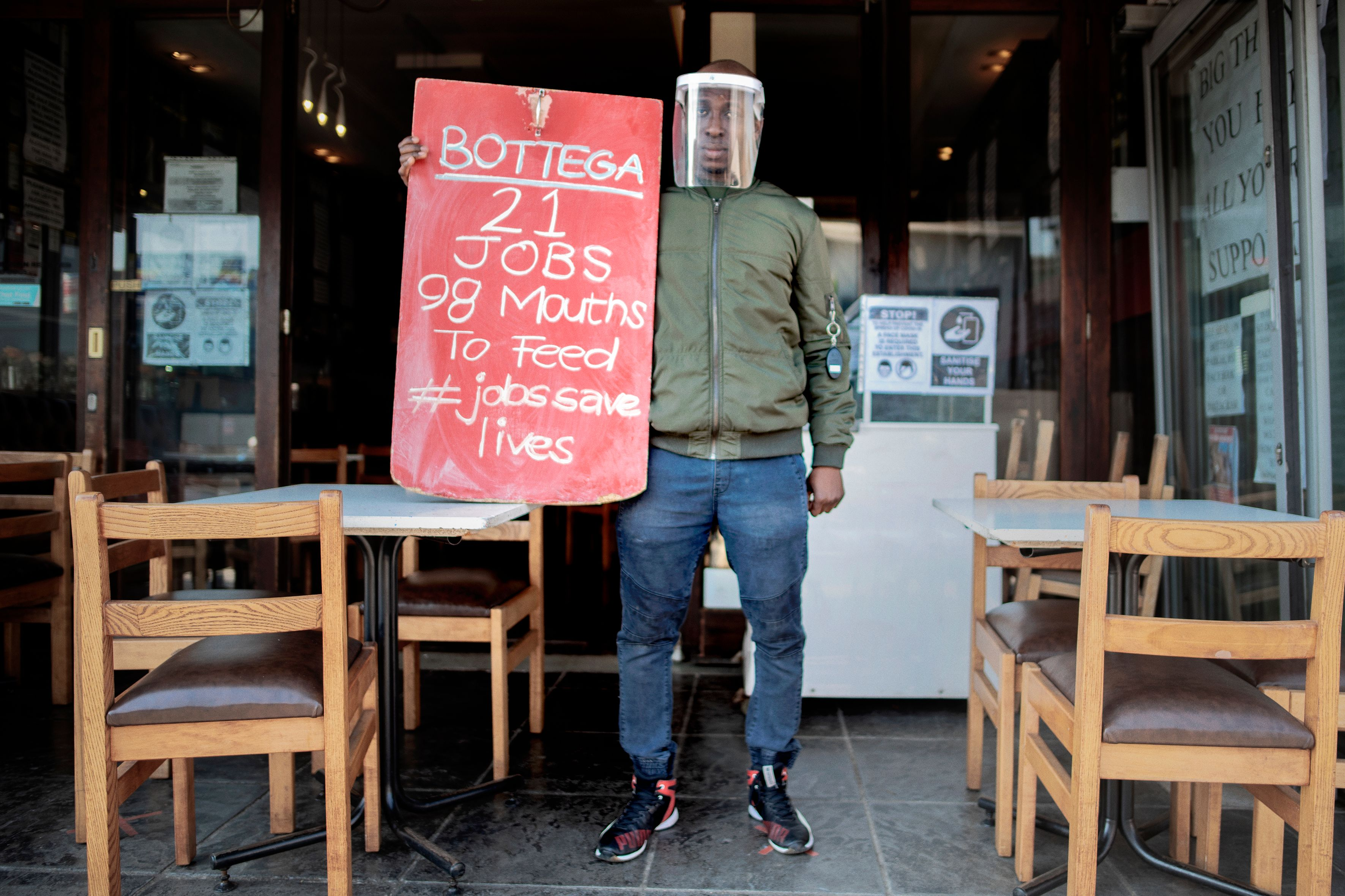 TOPSHOT - The manager of a restaurant in Parkhurst, Johannesburg, holds a banner during a national protest, organised by Restaurant Association of South Africa (RASA), against the national lockdown regulations the South African government has issued to fight the rise of COVID-19 coronavirus cases, on July 22, 2020. - The reintroduction on the ban on alcohol sales and a night curfew by the South African government will have a negative economic impact on the hospitality industry. (Photo by Luca Sola / AFP) (Photo by LUCA SOLA/AFP via Getty Images)