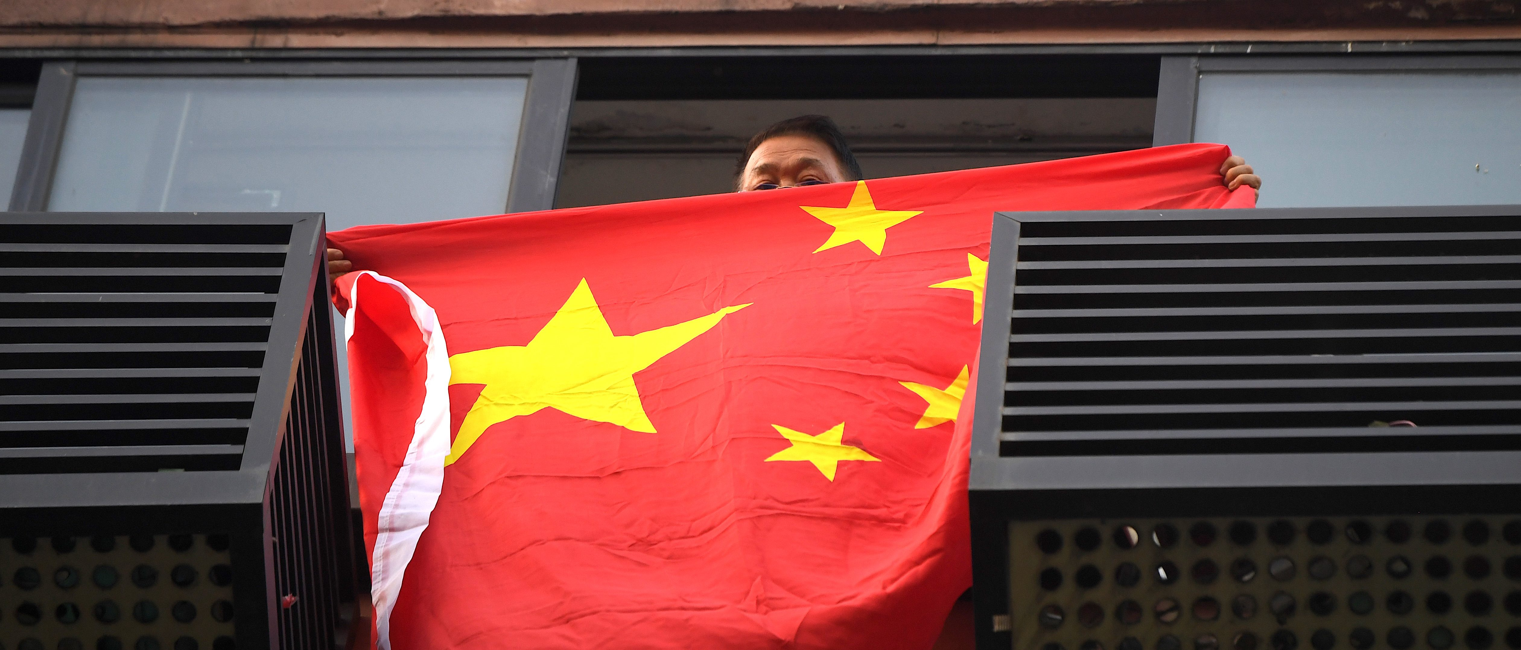 A resident unfurls the Chinese national flag from his building window in front of the US consulate in Chengdu, southwestern China's Sichuan province, on July 26, 2020. - The Chengdu mission was ordered shut in retaliation for the forced closure of Beijing's consulate in Houston, Texas, with both sides alleging the other had endangered national security. (NOEL CELIS/AFP via Getty Images)
