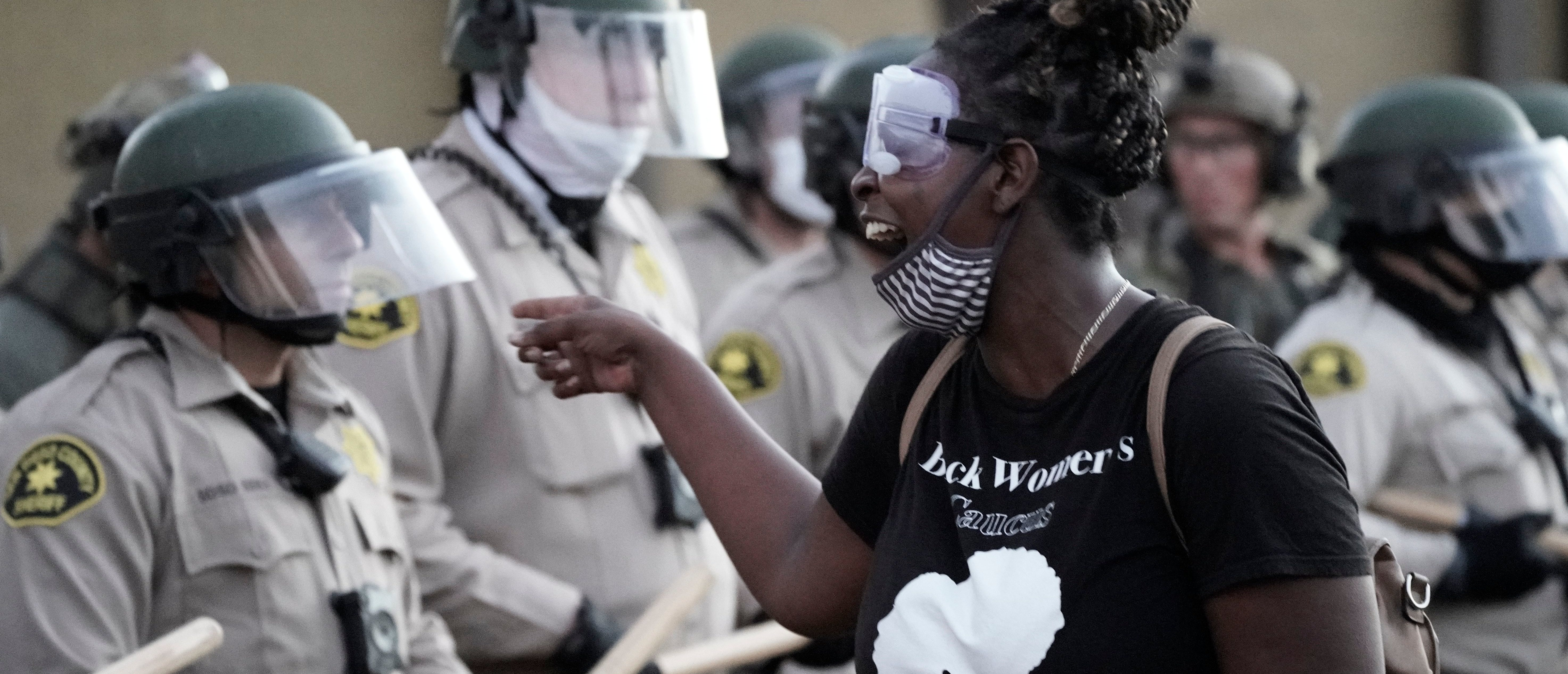 A demonstrator shouts at San Diego Sheriff Department deputies during a Black Lives Matter protest against racial injustice and police brutality in La Mesa, California, on August 1, 2020. (Photo by Bing GUAN / AFP) (Photo by BING GUAN/AFP via Getty Images)