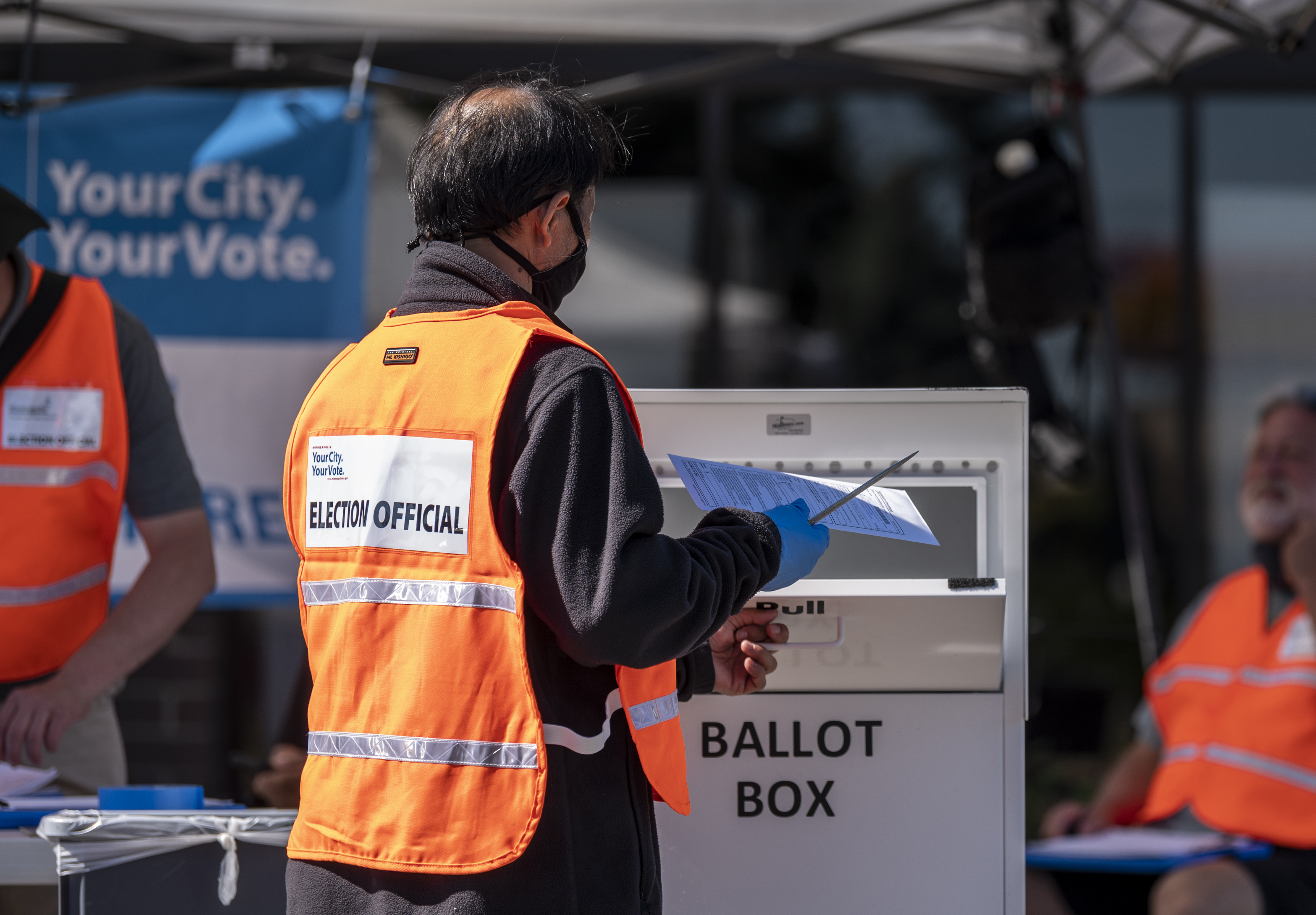 An election judge drops a ballot in a ballot box at a drive through drop-off for absentee ballots on August 11, 2020 in Minneapolis, Minnesota. (Stephen Maturen/Getty Images)