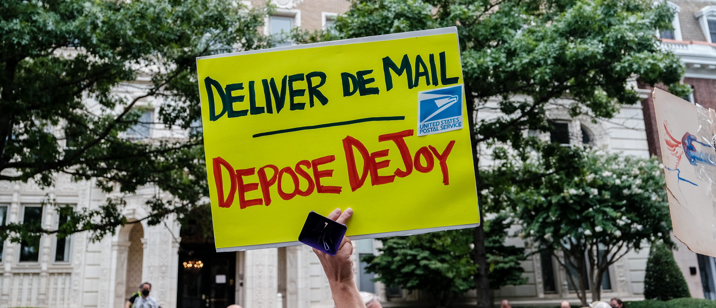 WASHINGTON, DC - AUG. 15: Demonstrators gather outside of the condo of President Donald Trump donor and current U.S. Postmaster General Louis Dejoy on Aug. 15, 2020 in Washington, DC. The protests are in response to a recent statement by President Trump to withhold USPS funding that would ensure that the post office would be unable handle mail-in voting ballots for the upcoming 2020 Election. (Photo by Michael A. McCoy/Getty Images)