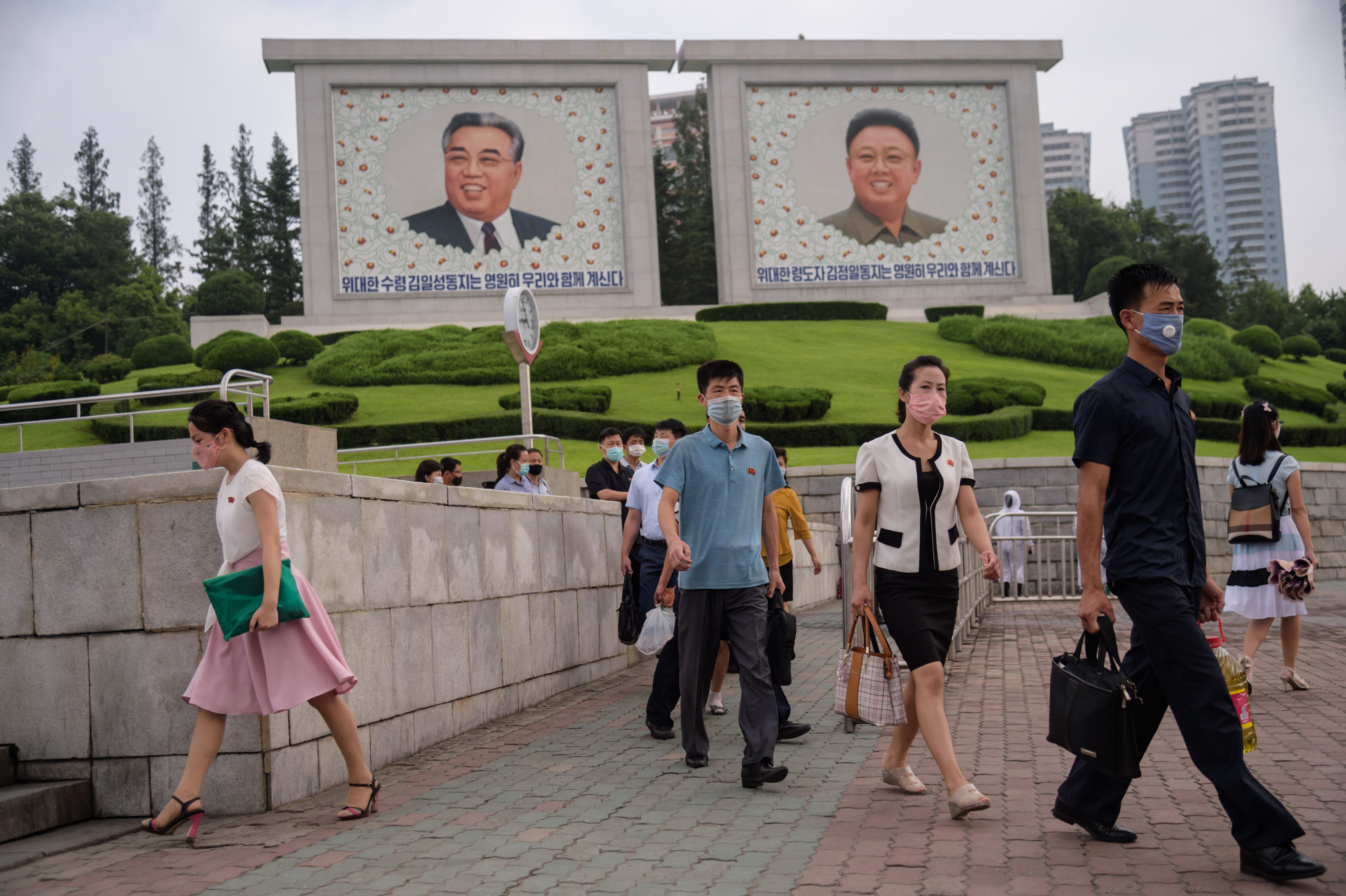 Pedestrians walk before the portraits of late North Korean leaders Kim Il Sung and Kim Jong Il, in central Pyongyang on August 19, 2020. (Photo by KIM Won Jin / AFP) (Photo by KIM WON JIN/AFP via Getty Images)