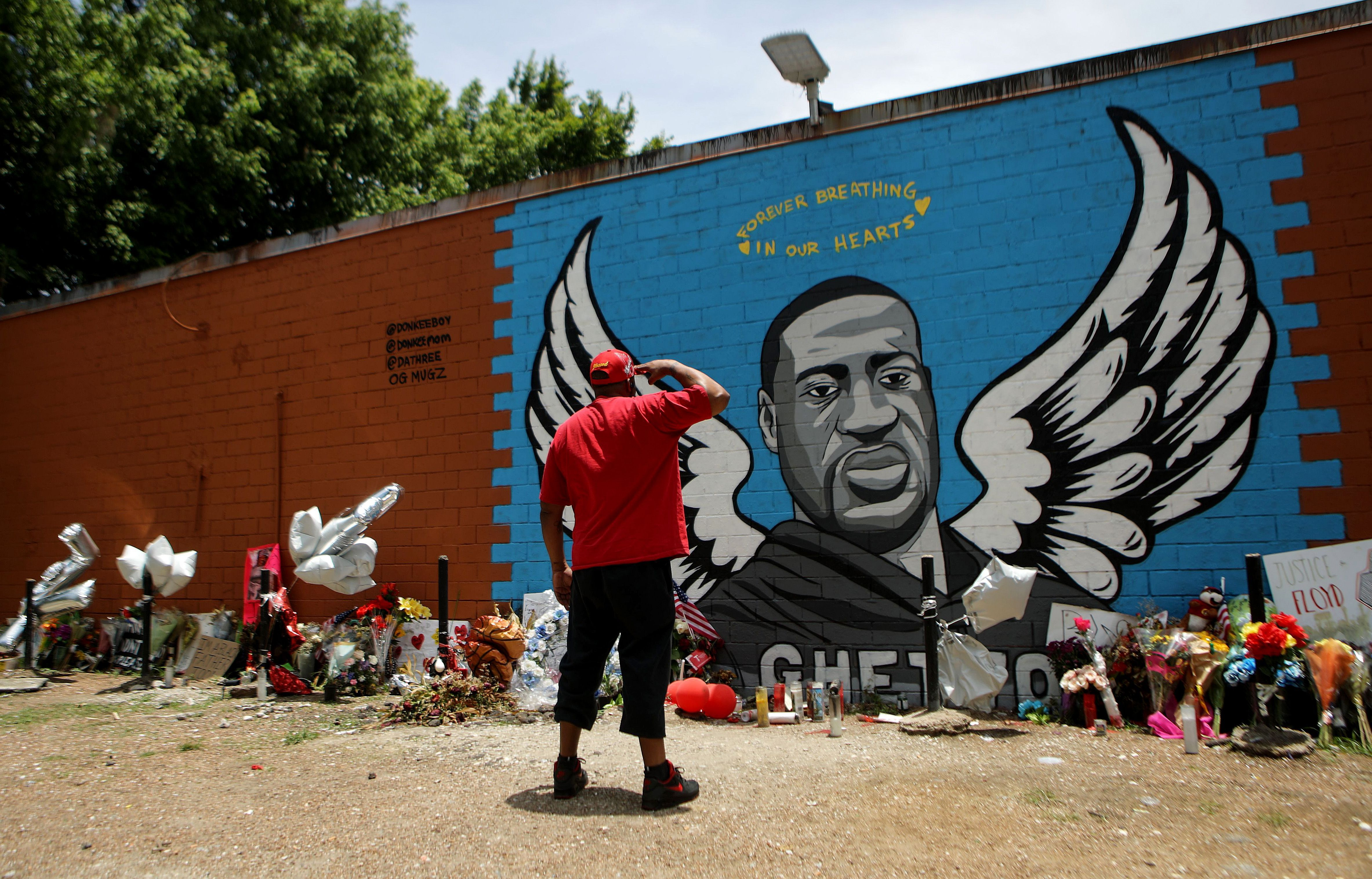 HOUSTON, TEXAS - JUNE 10: A man salutes at a mural dedicated to George Floyd, across the street from the Cuney Homes housing project in Houston's Third Ward, where Floyd grew up and later mentored young men, on June 10, 2020 in Houston, Texas. George Floyd died on May 25th when he was in Minneapolis police custody, sparking nationwide protests. A white police officer, Derek Chauvin, has been charged with second-degree murder, with the three other officers involved facing other charges. (Photo by Mario Tama/Getty Images)