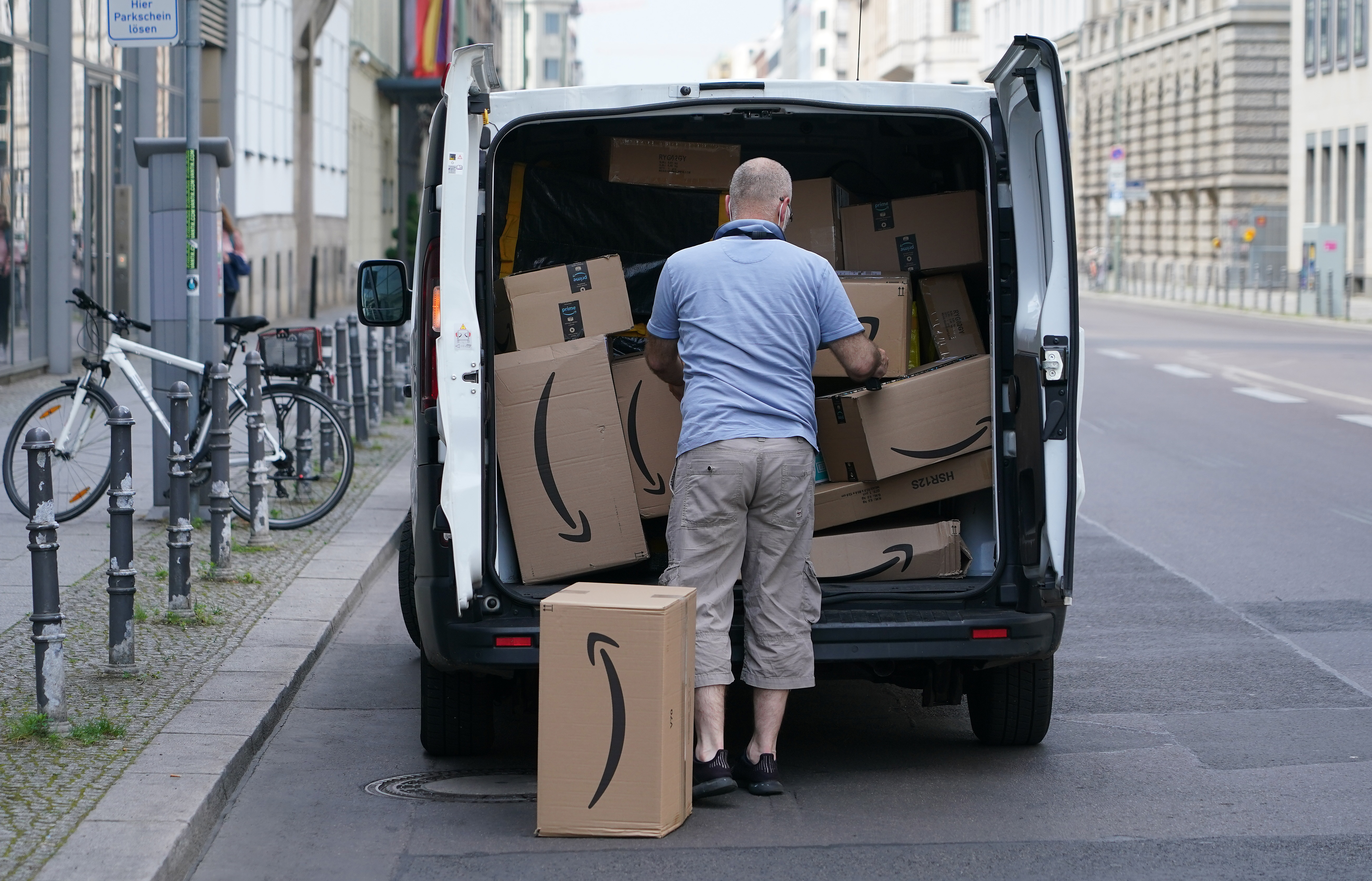 A courier unloads Amazon packages during a delivery on June 18, 2020 in Berlin, Germany. Amazon has expanded rapidly in Germany and now has at least 13 Amazon warehouses nationwide. (Photo by Sean Gallup/Getty Images)