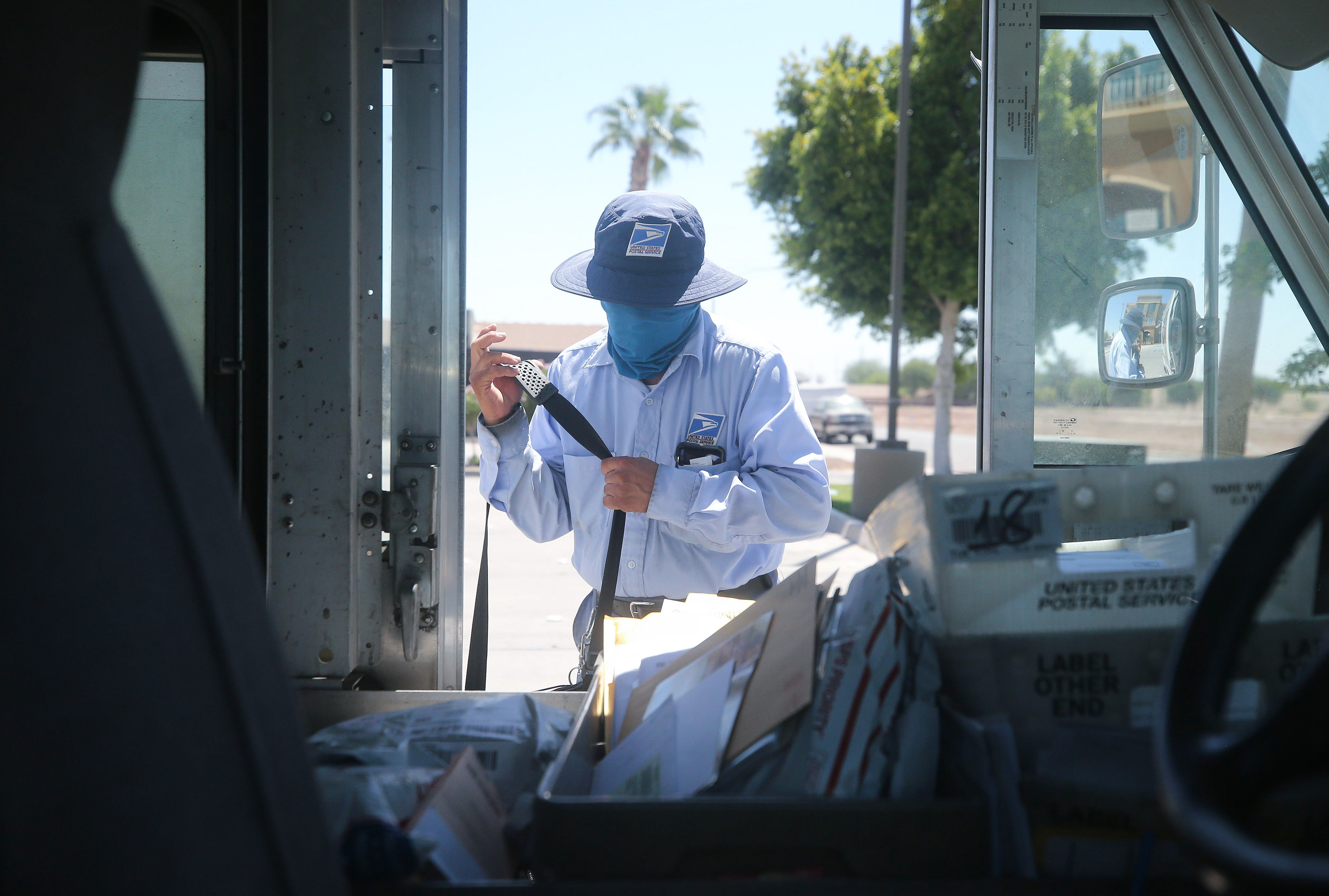A USPS postal worker wears a face mask amid the coronavirus pandemic in hard-hit Imperial County on July 21, 2020 in El Centro, California. (Mario Tama/Getty Images)