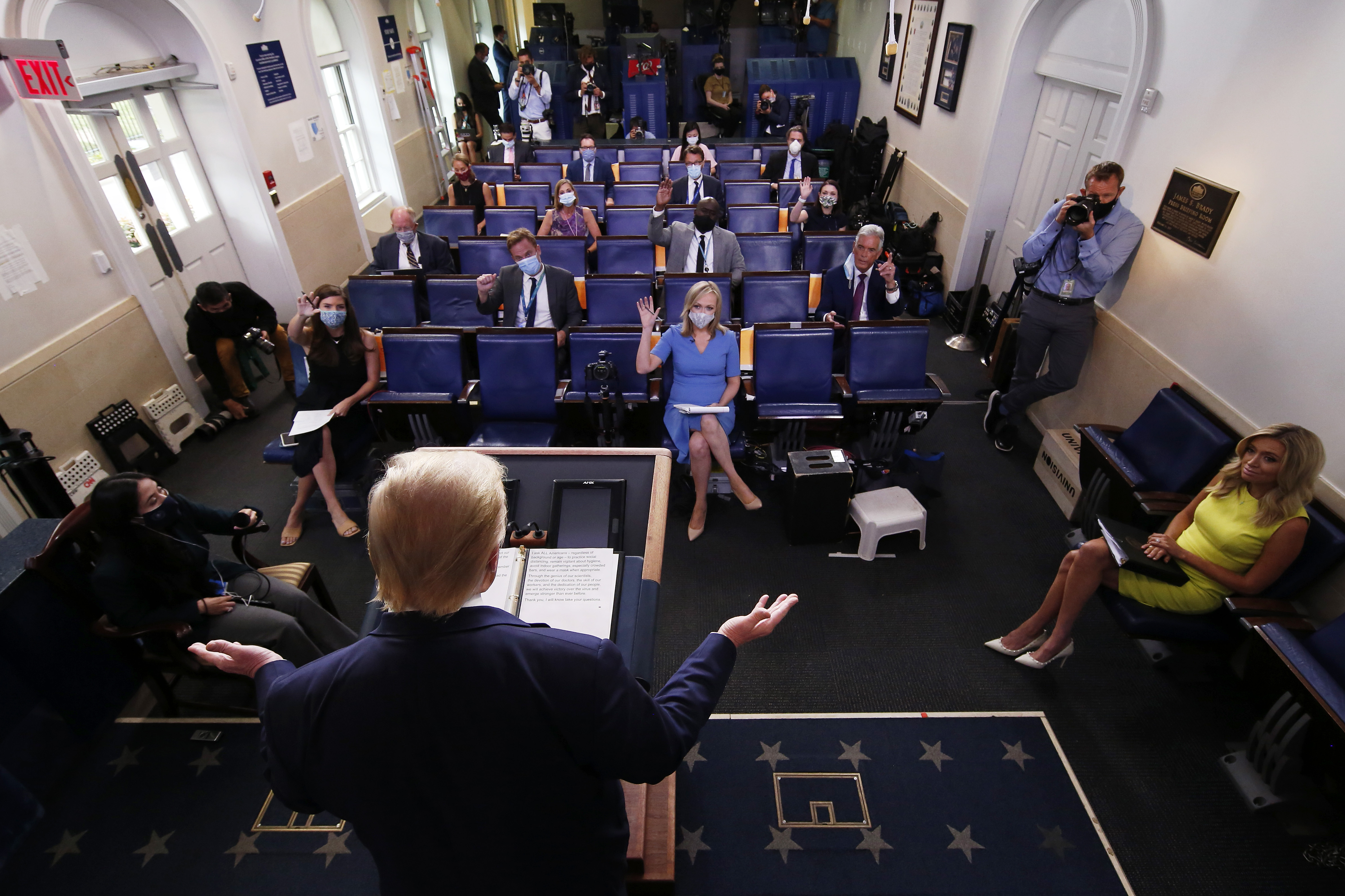 WASHINGTON, DC - JULY 28: U.S. President Donald Trump speaks as White House Press Secretary Kayleigh McEnany (R) looks on during a news briefing at the James Brady Press Briefing Room of the White House July 28, 2020 in Washington, DC. The president announced that Eastman Kodak will receive a loan to manufacture ingredients used in pharmaceuticals. (Photo by Alex Wong/Getty Images)