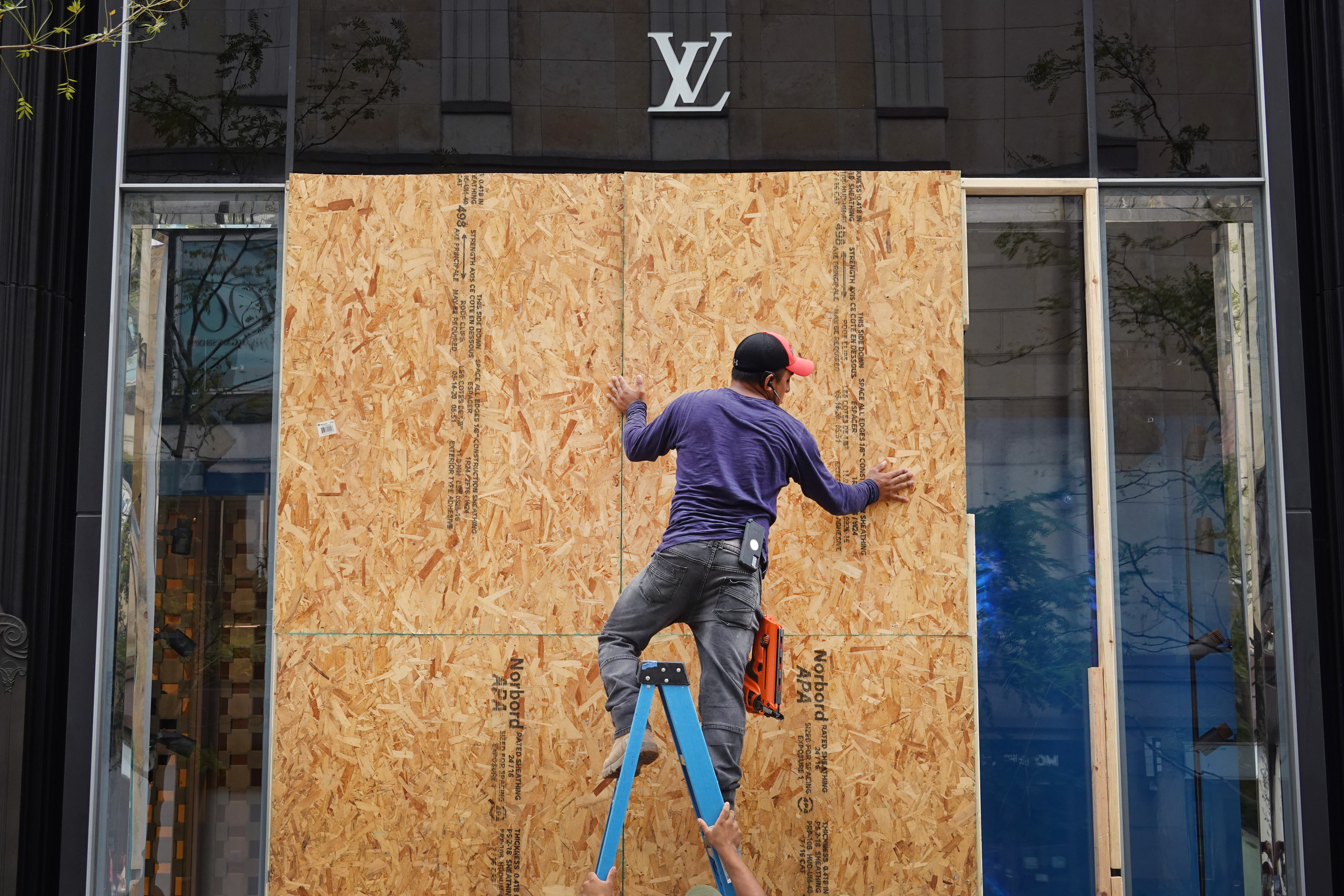 Workers make repairs to the Louis Vuitton store after it was looted on August 10, 2020 in Chicago, Illinois. Police made more than 100 arrests during the night as widespread looting and disorderly conduct was reported downtown and other areas of the city. Officials believe the violence had apparently grown out of a shoot out between police and a suspect. (Photo by Scott Olson/Getty Images)