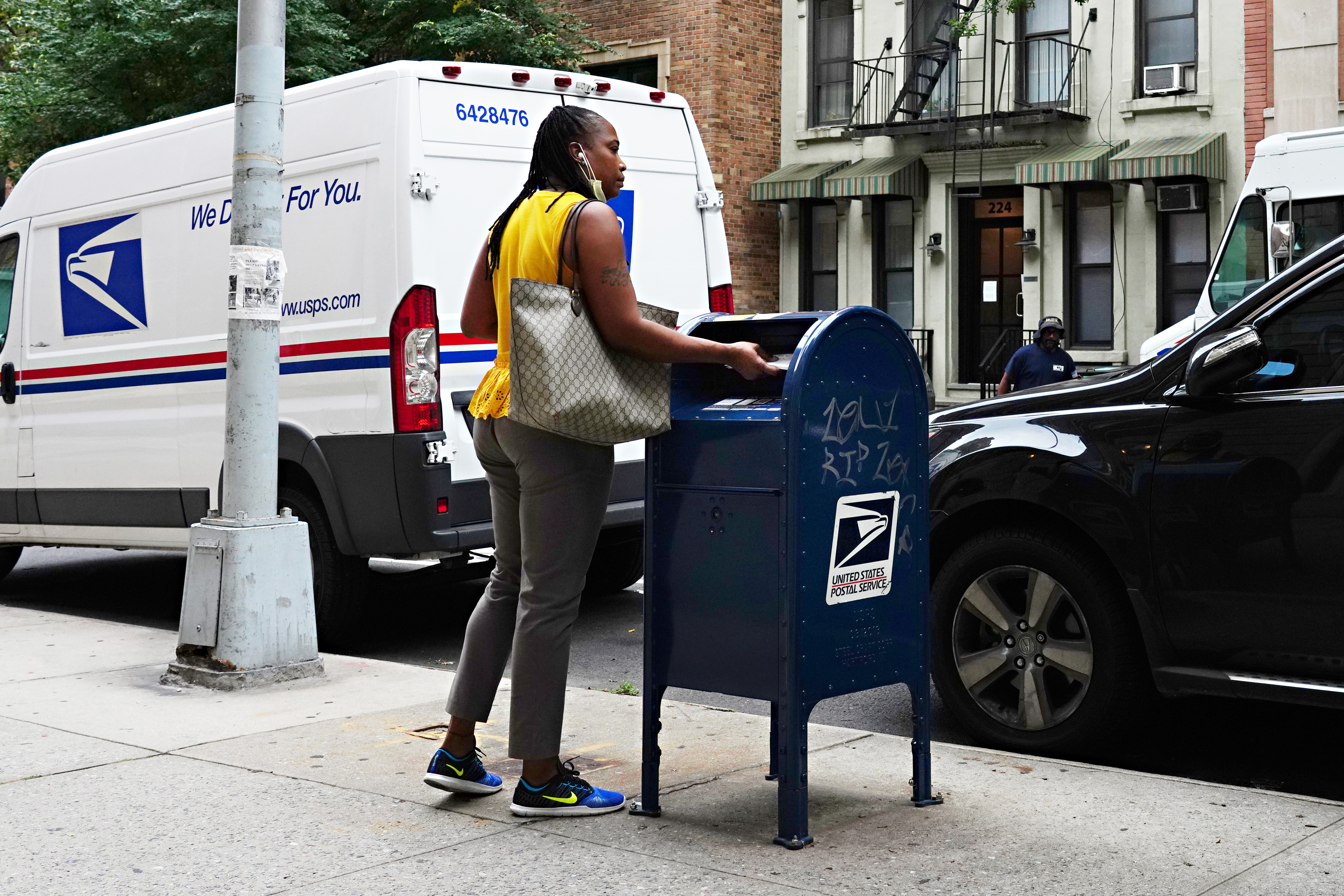 A woman wearing a protective mask at her chin uses a USPS mailbox as the city continues Phase 4 of re-opening following restrictions imposed to slow the spread of coronavirus on August 17, 2020 in New York City. (Cindy Ord/Getty Images)