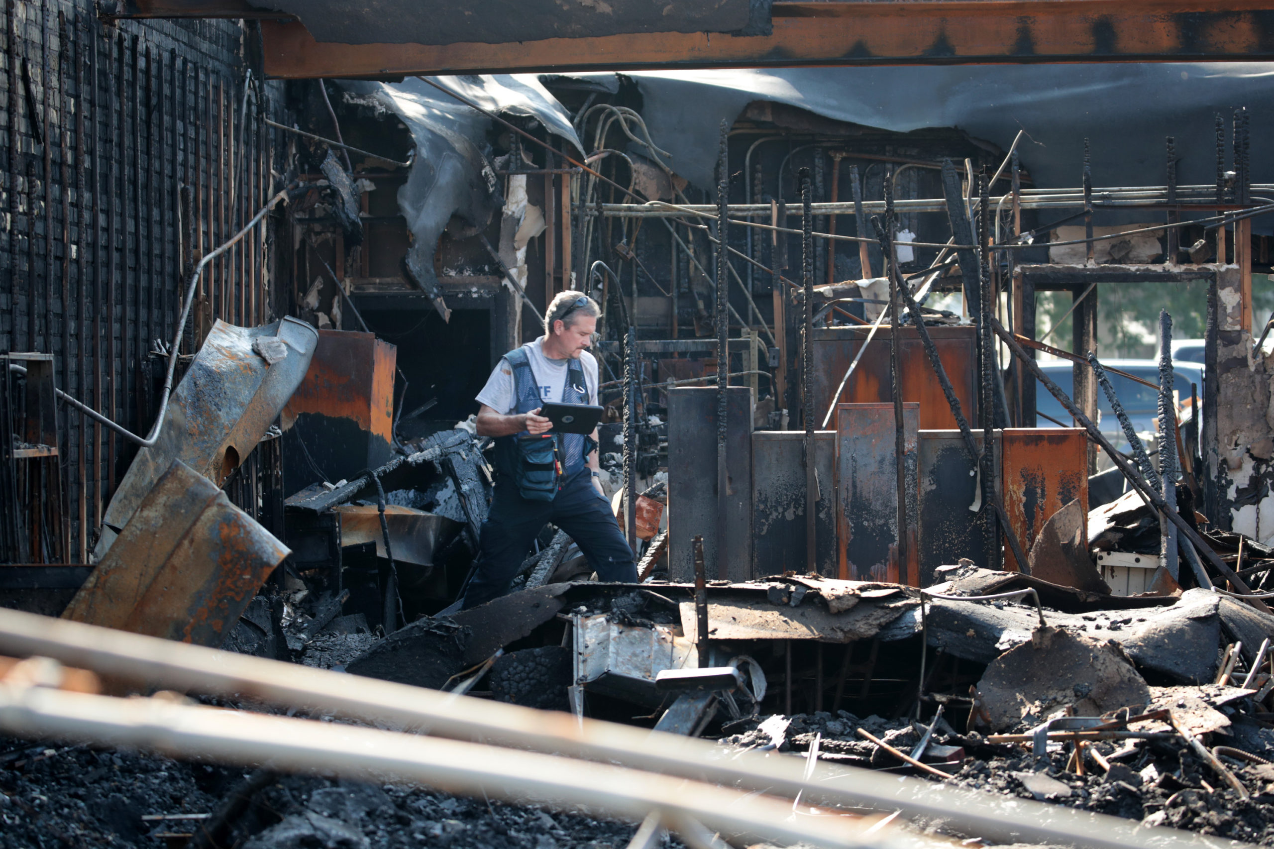 KENOSHA, WISCONSIN - AUGUST 28: An ATF agent collects evidence in a burned out store that was destroyed during recent rioting following the shooting of Jacob Blake on August 28, 2020 in Kenosha, Wisconsin. Blake remains in the hospital after being shot seven times in the back in front of his three children by a police officer. (Photo by Scott Olson/Getty Images)