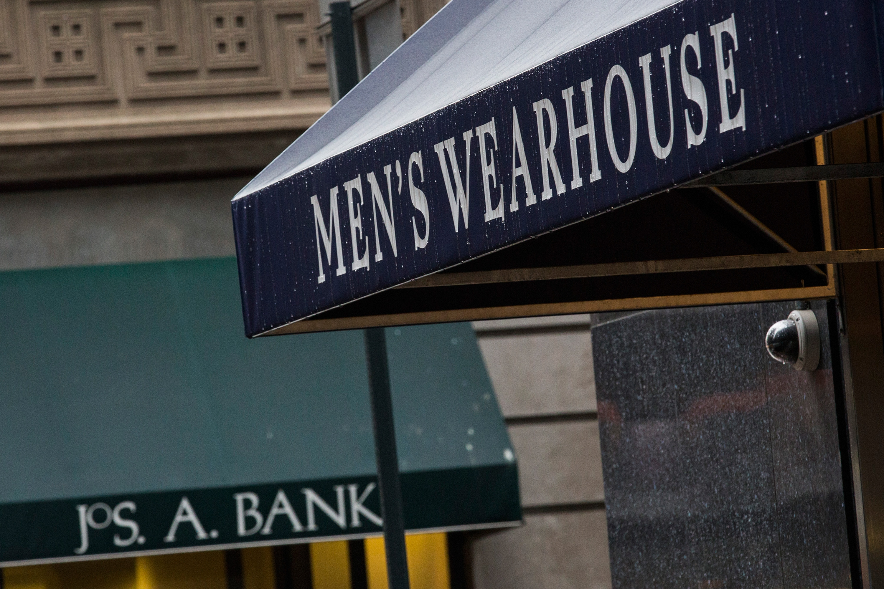 Men's Warehouse and Jos. A Bank storefronts are seen next to each other on January 6, 2014 in New York City. Men's Warehouse is currently pursuing a hostile takeover of competitor Jos. A. Bank, which also sells men's suits and buisness wear. (Photo by Andrew Burton/Getty Images)