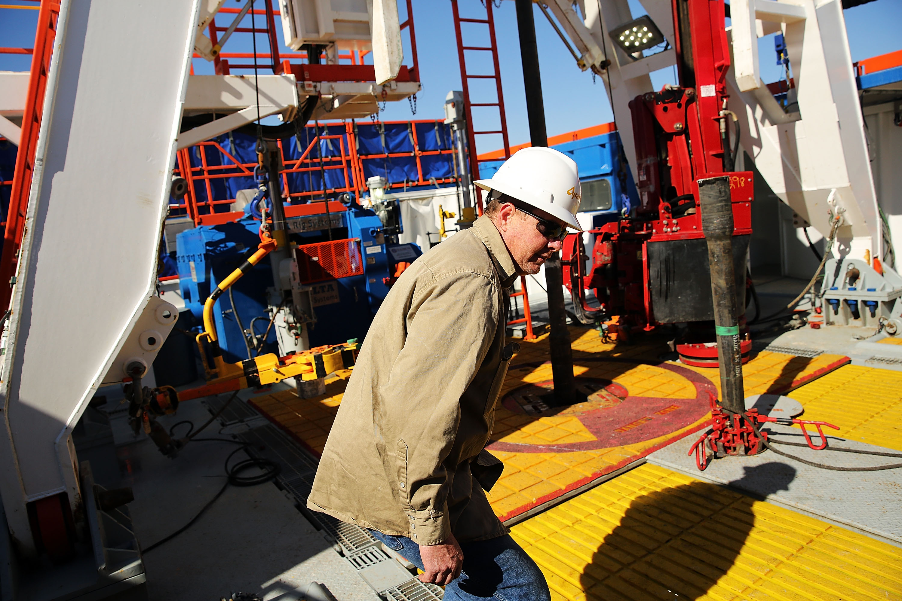 A worker with Apache Corp. is viewed at the Patterson 298 natural gas fueled drilling rig on land in the Permian Basin in 2015 in Mentone, Texas. (Spencer Platt/Getty Images)