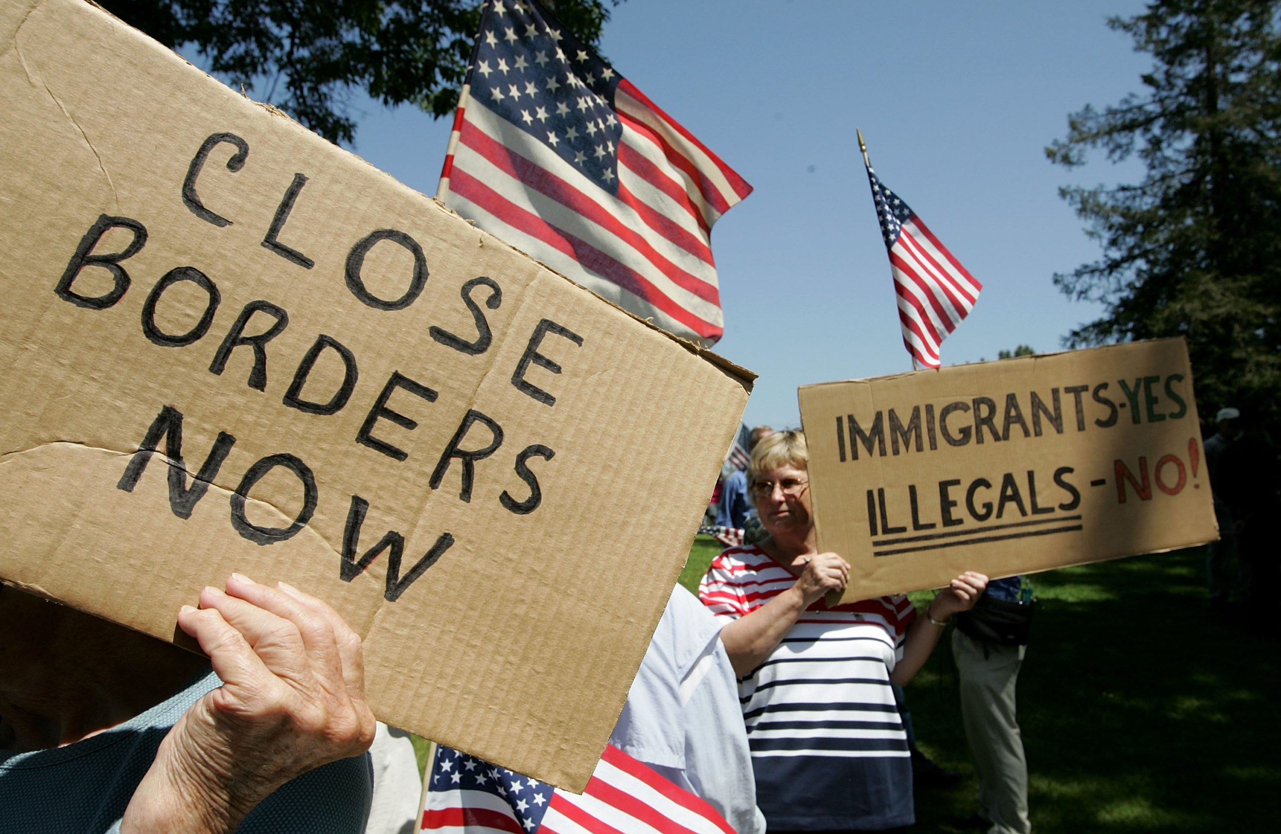 SANTA CLARA, CA - MAY 05: Anti-immigration demonstrators hold signs and American flags during an anti-immigration rally May 5, 2006 in Santa Clara, California. Dozens of anti-immigration demonstrators held a rally as similar rallies were held across the country on Cinco de Mayo to protest illegal immigrants. (Photo by Justin Sullivan/Getty Images)