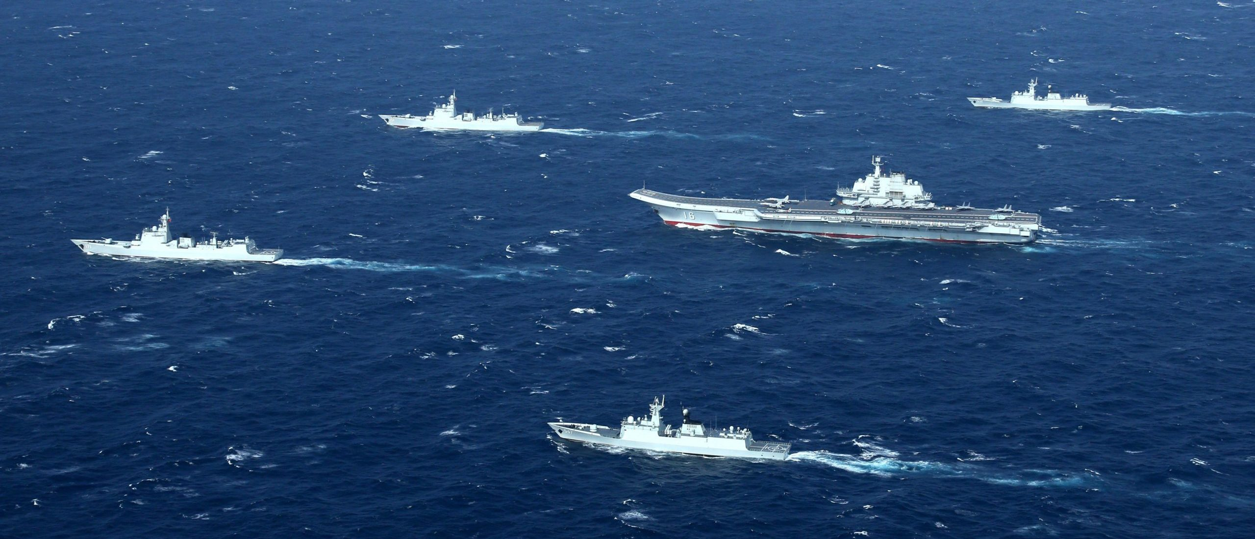 This aerial photo taken on January 2, 2017 shows a Chinese navy formation, including the aircraft carrier Liaoning (C), during military drills in the South China Sea. The aircraft carrier is one of the latest steps in the years-long build-up of China's military, as Beijing seeks greater global power to match its economic might and asserts itself more aggressively in its own backyard. / AFP / STR / China OUT (Photo credit should read STR/AFP via Getty Images)