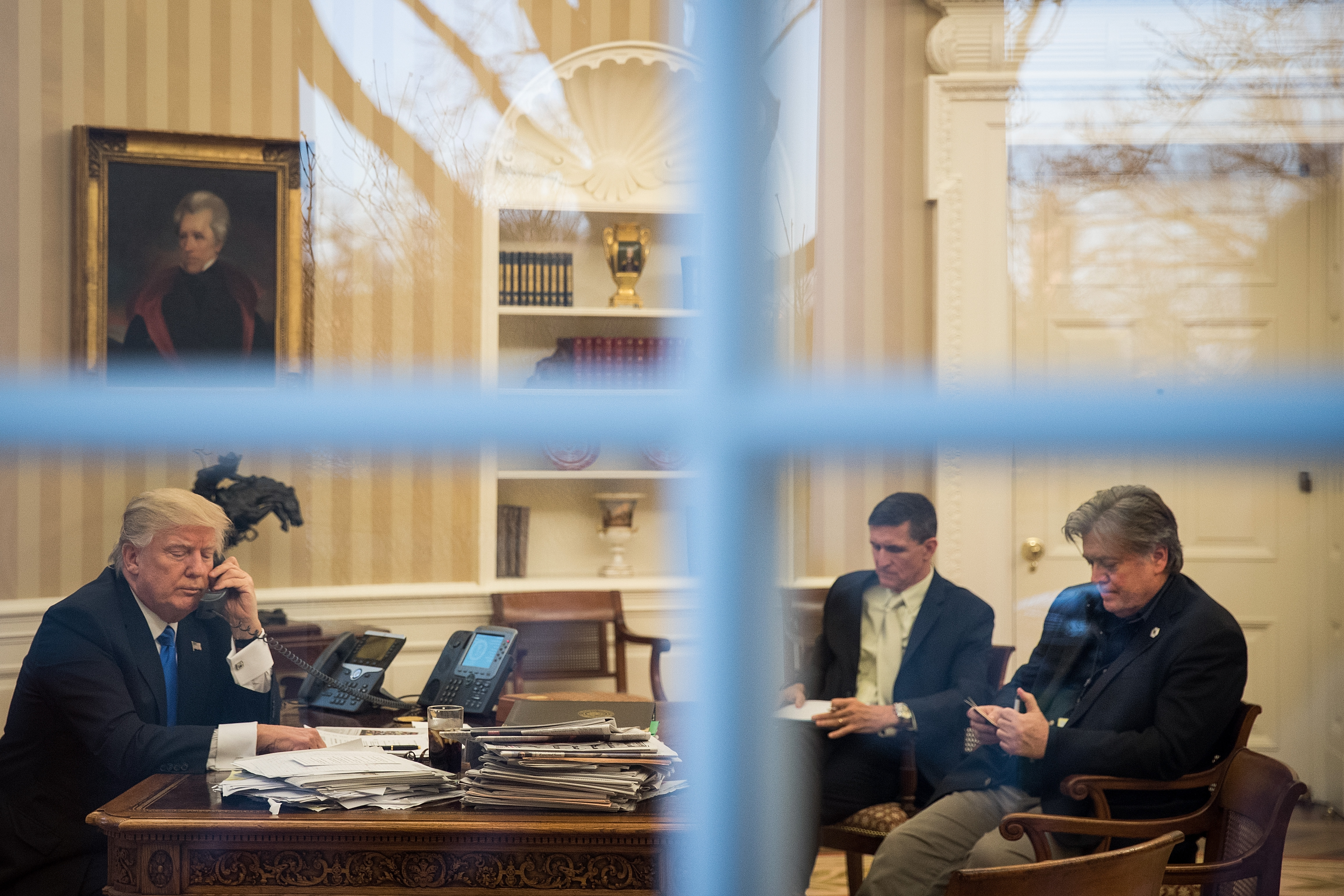 WASHINGTON, DC - JANUARY 28: President Donald Trump speaks on the phone with Australian Prime Minister Malcolm Turnbull in the Oval Office of the White House, January 28, 2017 in Washington, DC. Also pictured at right, National Security Advisor Michael Flynn and White House Chief Strategist Steve Bannon. On Saturday, President Trump is making several phone calls with world leaders from Japan, Germany, Russia, France and Australia. (Photo by Drew Angerer/Getty Images)