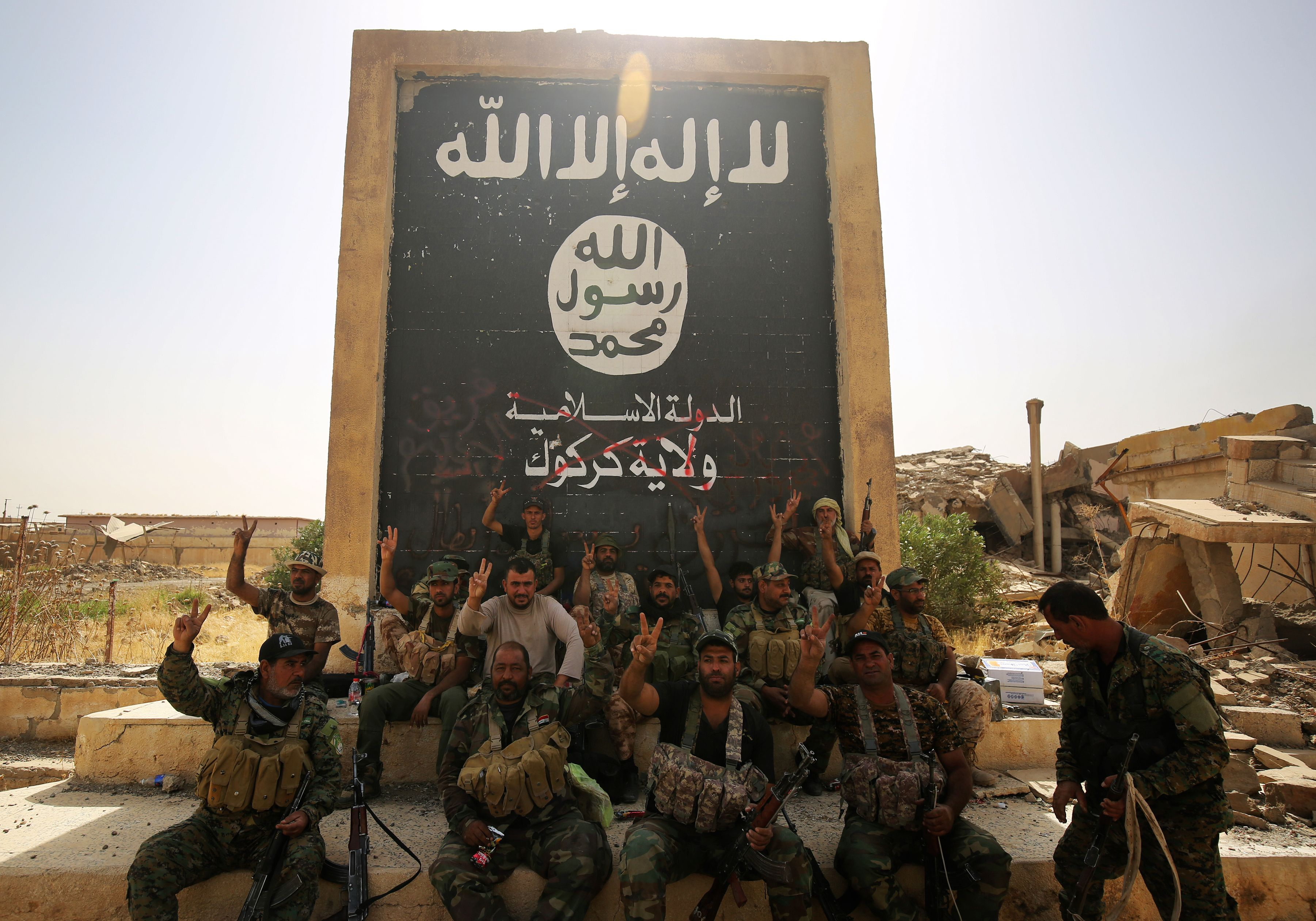 Fighters from the Hashed al-Shaabi (Popular Mobilisation units), backing the Iraqi forces, pose in front of a mural depicting the emblem of the Islamic State (IS) group as troops advance through Hawija on October 5, 2017, after retaking the city from Islamic State (IS) group fighters. (AHMAD AL-RUBAYE/AFP via Getty Images)