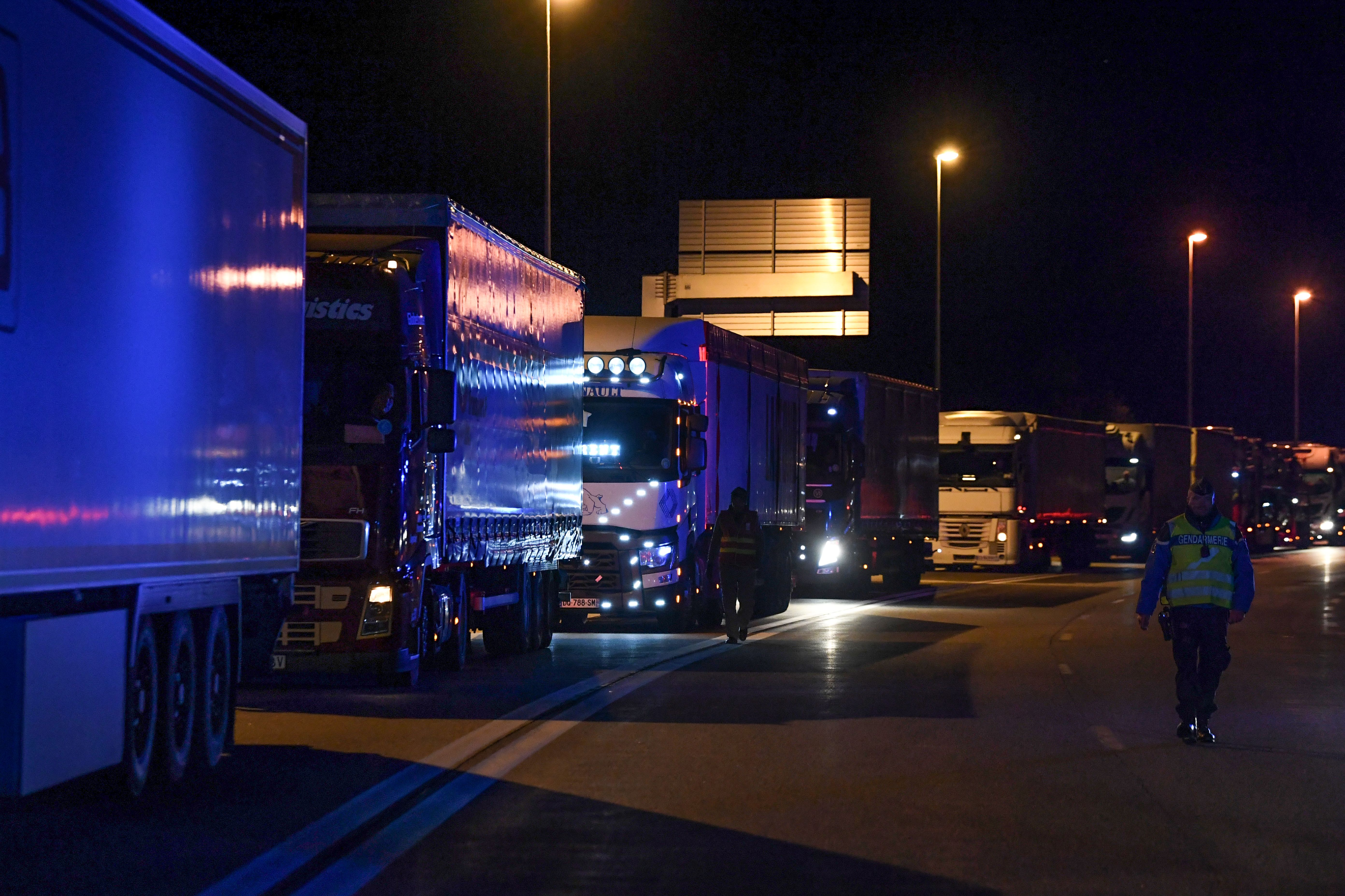A Gendarme (R) walks along transport trucks lined up during a blockade to access to the Frejus tunnel, early on November 21, 2017 close to the border between France and Italy in Modane. About 50 truck drivers were blocking on November 21 the tunnel access, a major traffic route between France and Italy, to protest against the exclusion of road transport from the new European directive on posted workers. (Photo by Jean-Pierre Clatot/AFP via Getty Images)
