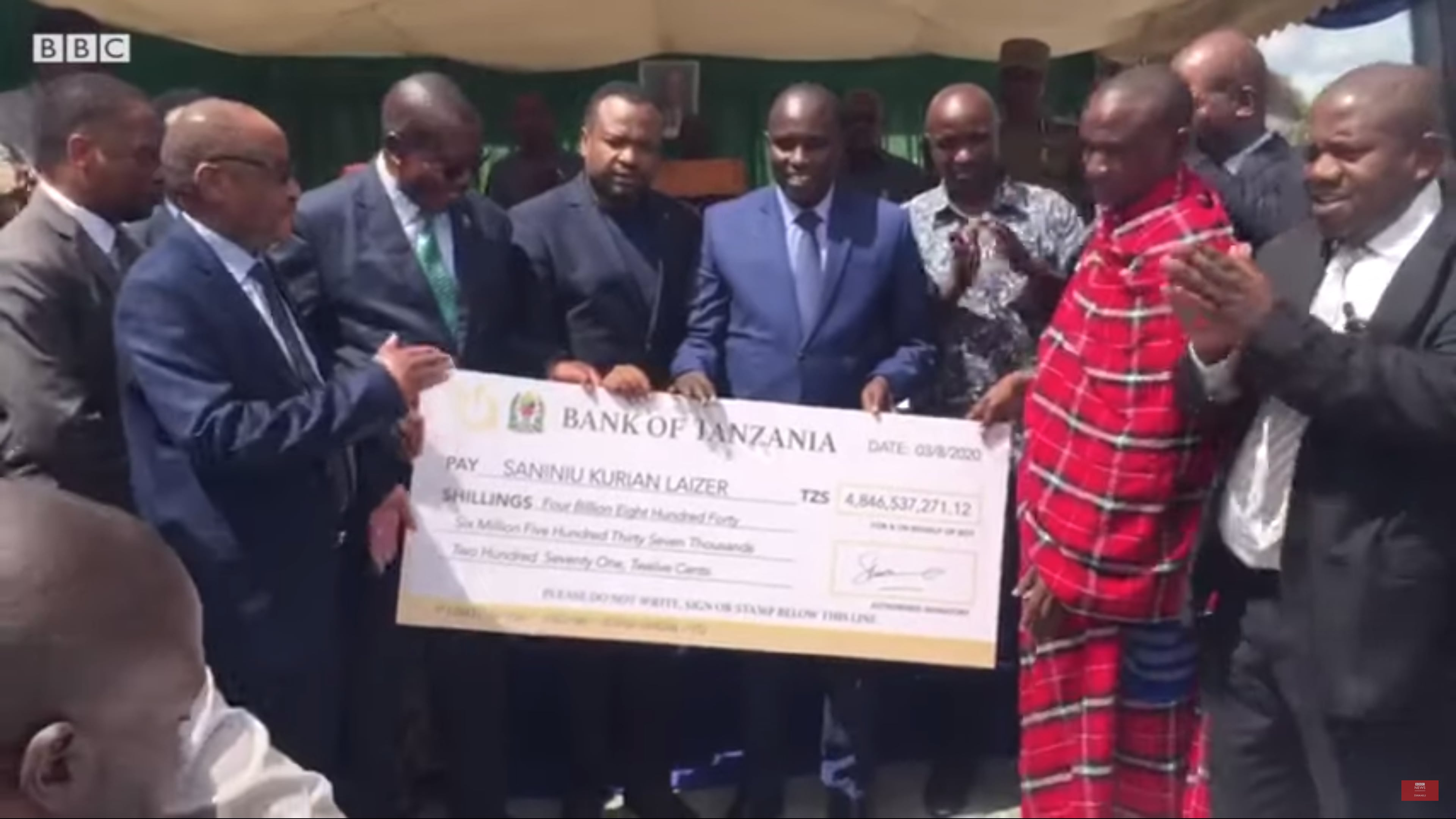 Tanzanian government officials hand Saniniu Laizer a check following his discovery of two rare Tanzanite gemstones in June. (BBC/Screenshot/YouTube)