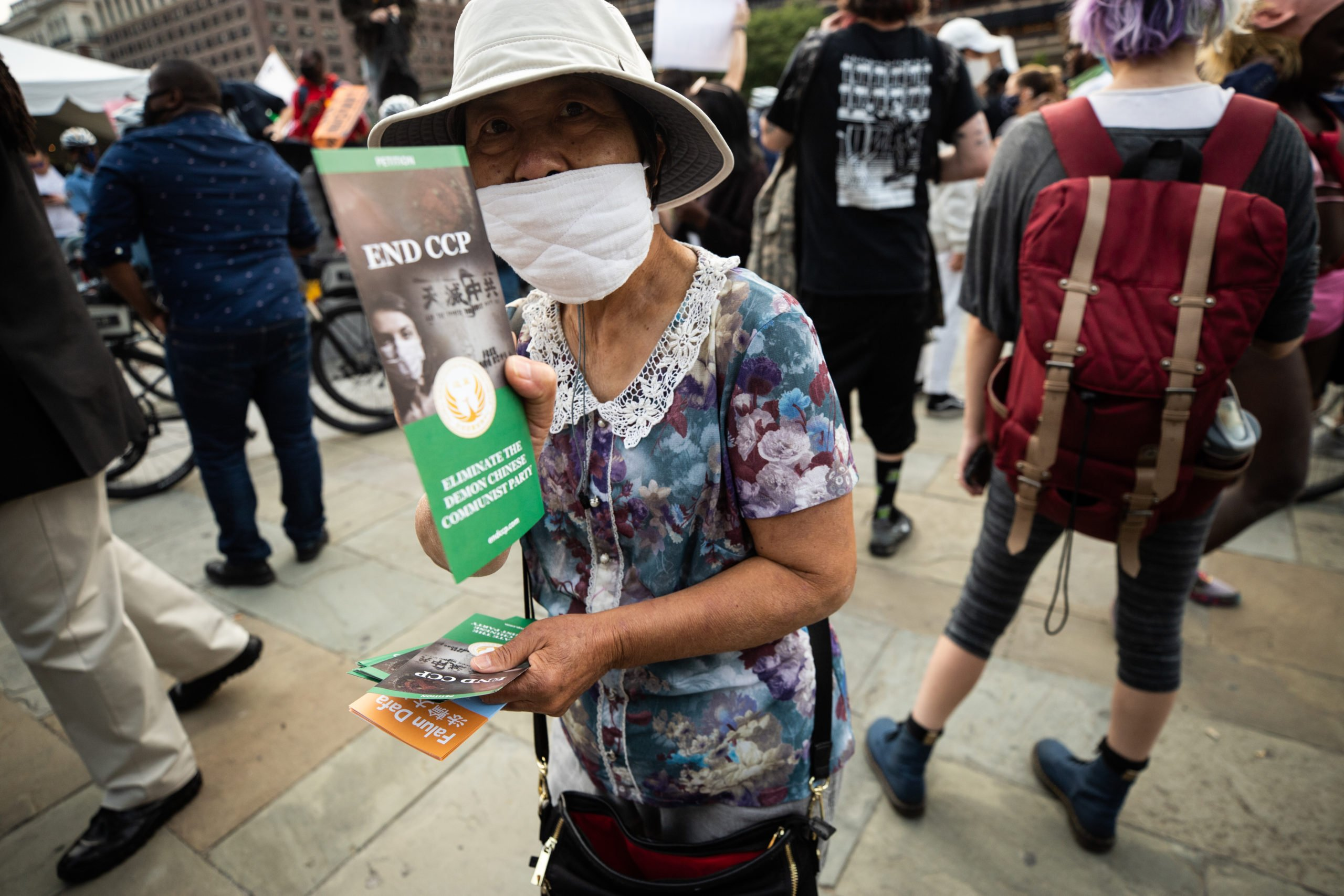 "A woman passes out brochures saying ""eliminate the Chinese communist party,"" in Philadelphia, Pennsylvania on Sept. 15, 2020. (Photo: Kaylee Greenlee / DCNF)"