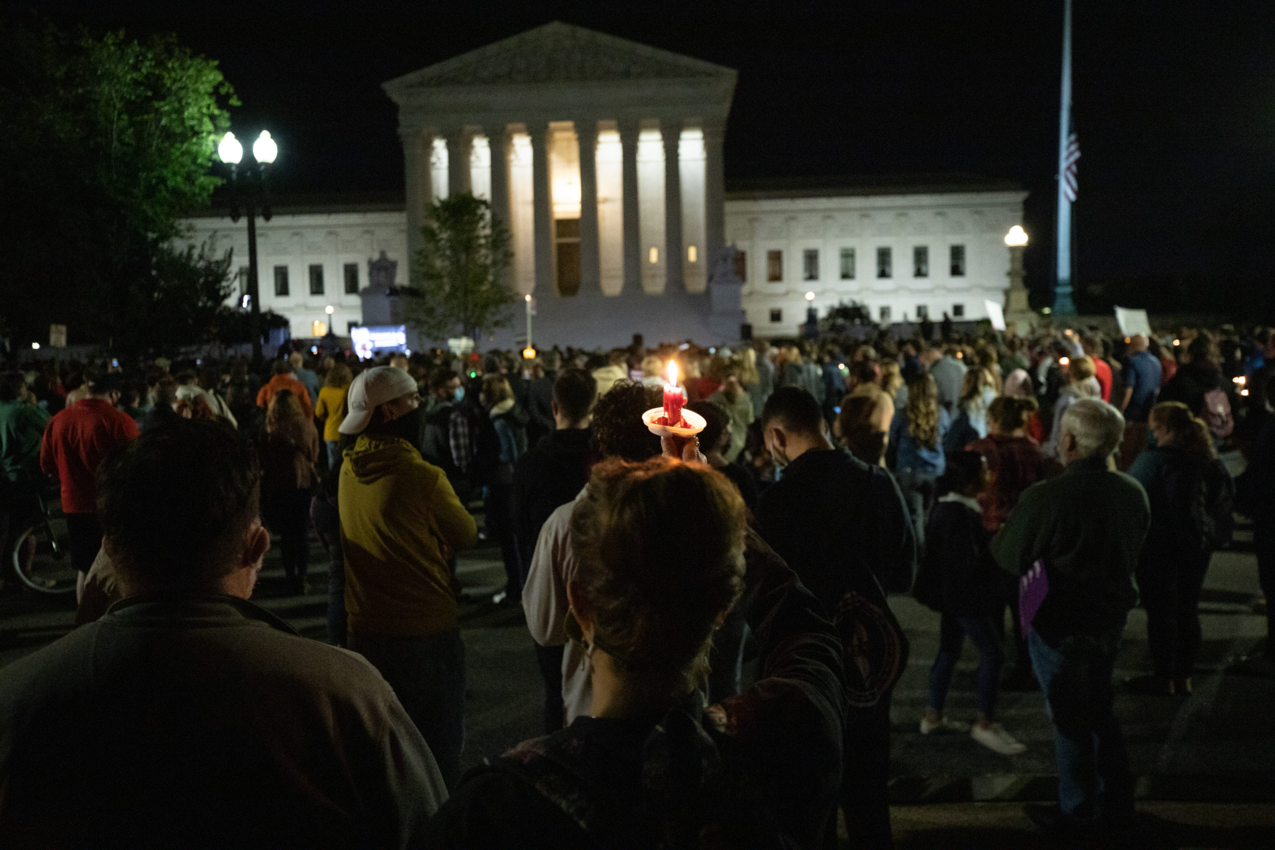 A woman holds a candle up towards the Supreme Court at a memorial honoring the late Justice Ruth Bader Ginsburg on Sept. 19, 2020. (Photo: Kaylee Greenlee / The DCNF)