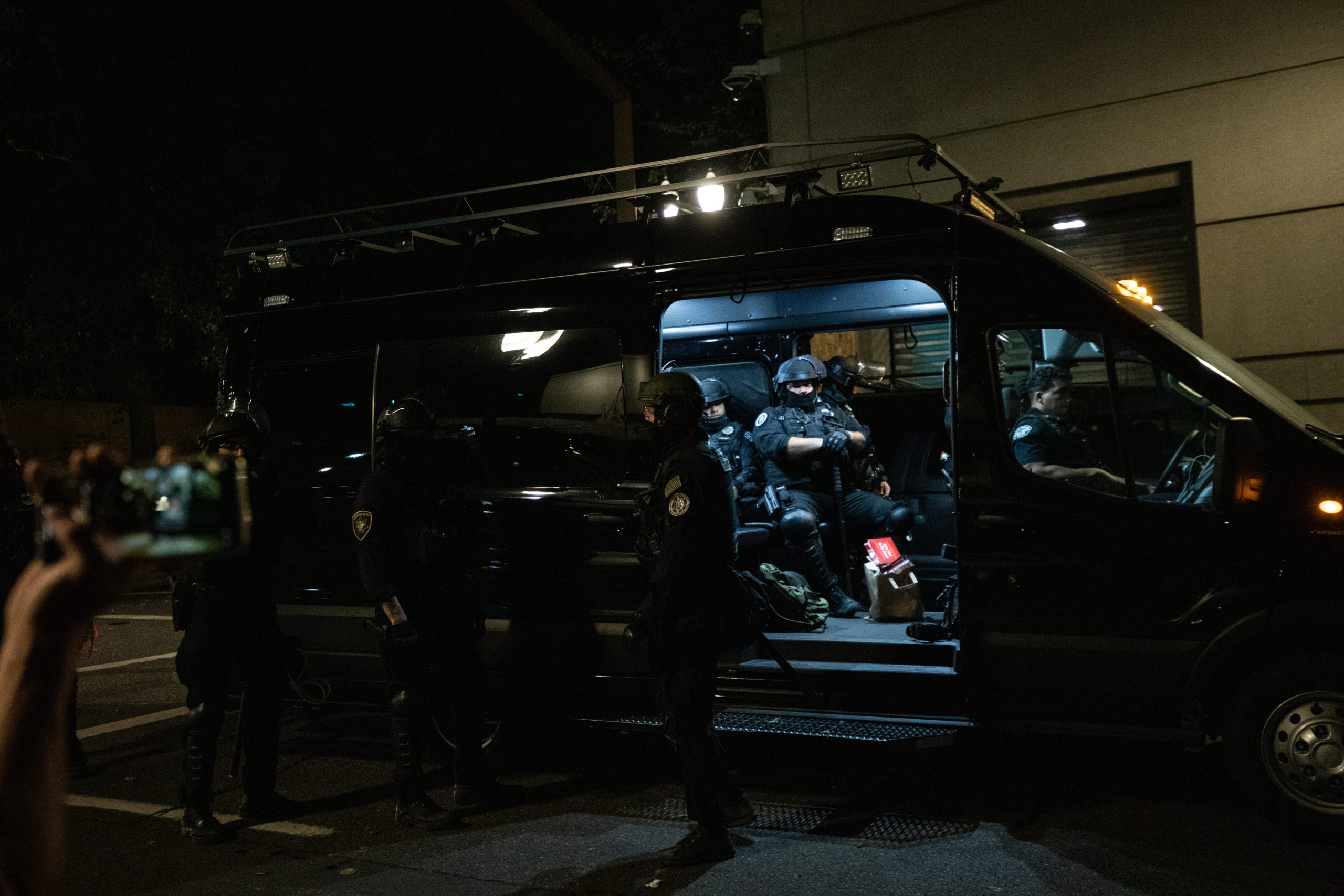 Police gather into an unmarked van outside of the Portland Police Bureau in Portland, Oregon, on Sept. 27, 2020. (Photo: Kaylee Greenlee / DCNF)