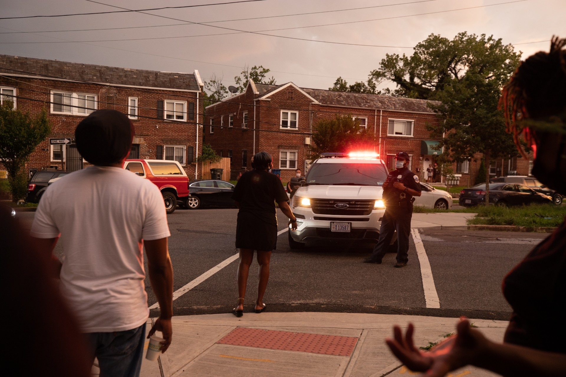 A woman confronts an officer near the southeast Washington D.C. crime scene where Metropolitan Police Department officers fatally shot a young black man Wednesday. (Kaylee Greenlee/Daily Caller News Foundation)
