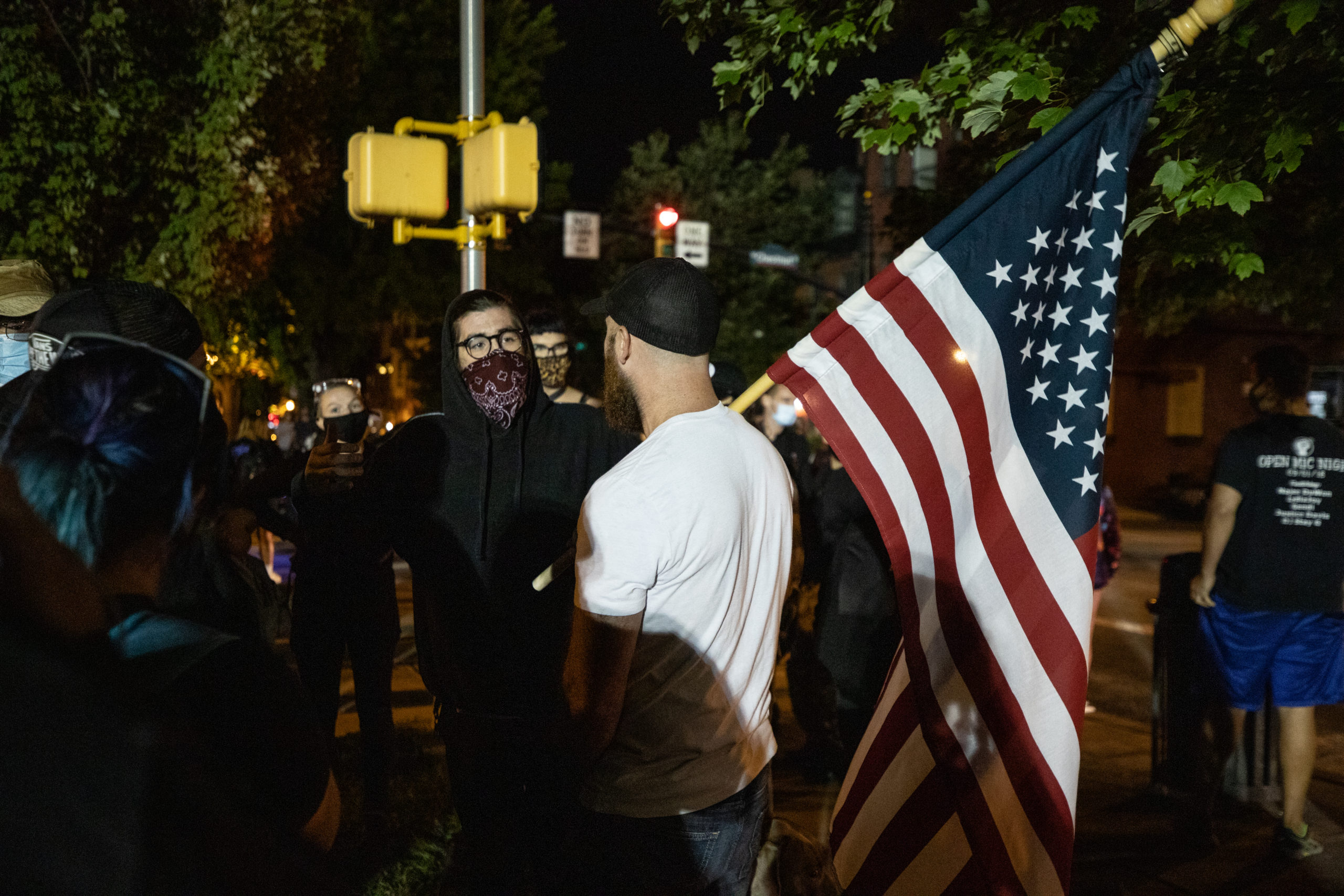 A man with an American flag talked with protesters throughout the night in Lancaster, Philadelphia on Sept. 14, 2020. (Photo - Kaylee Greenlee / Daily Caller News Foundation)