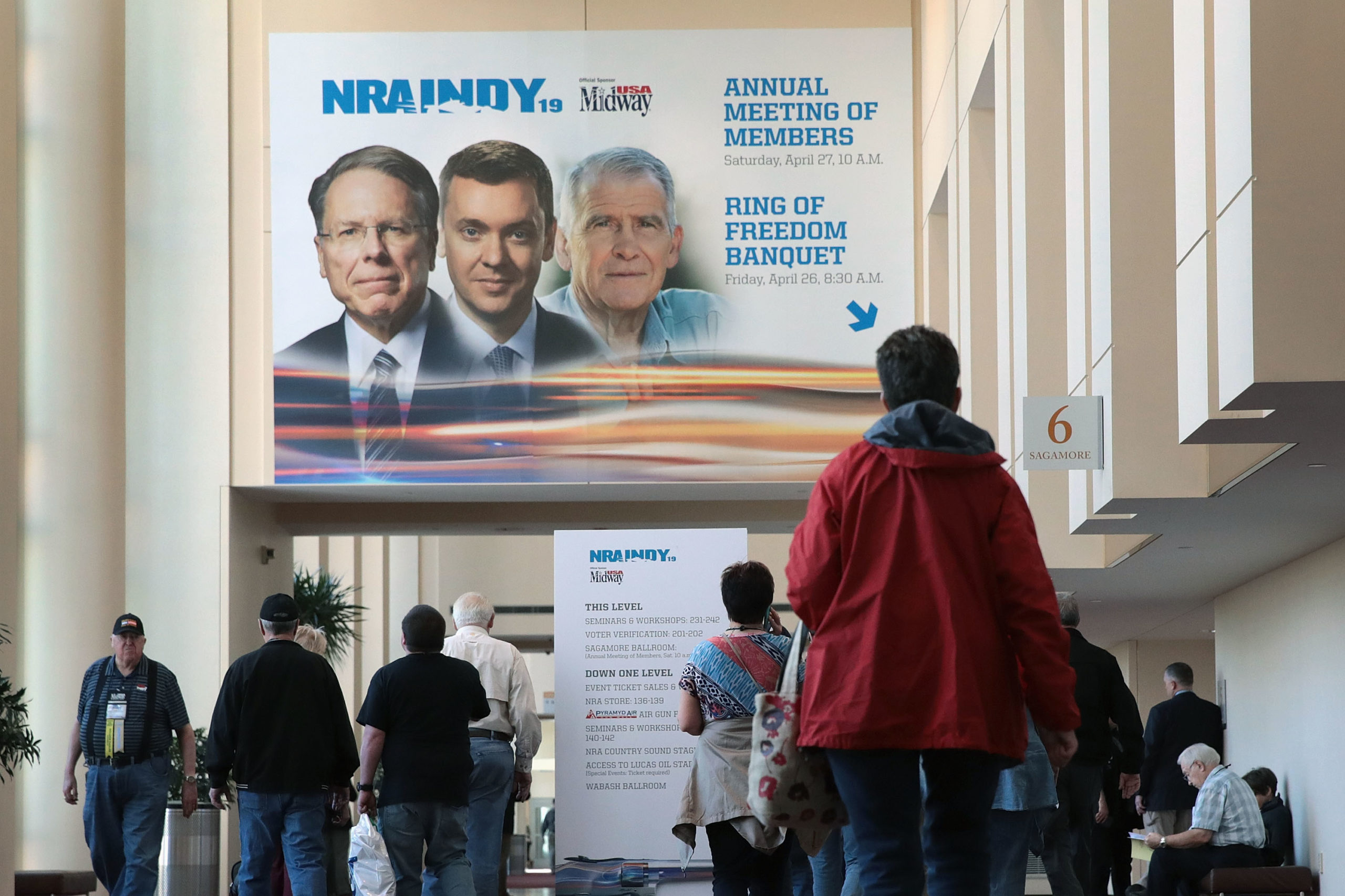 INDIANAPOLIS, INDIANA - APRIL 27: Guest walk under a poster featuring Wayne LaPierre (L), NRA vice president and CEO, Chris Cox (C), executive director of the NRA-ILA, and NRA president Oliver North outside a conference room where the NRA annual meeting of members was being held at the 148th NRA Annual Meetings & Exhibits on April 27, 2019 in Indianapolis, Indiana. A statement was read at the meeting announcing that NRA president Oliver North, whose seat at the head table remained empty at the event, would not serve another term. There have been recent reports of tension between LaPierre and North, with North citing financial impropriety within the organization. (Scott Olson/Getty Images)