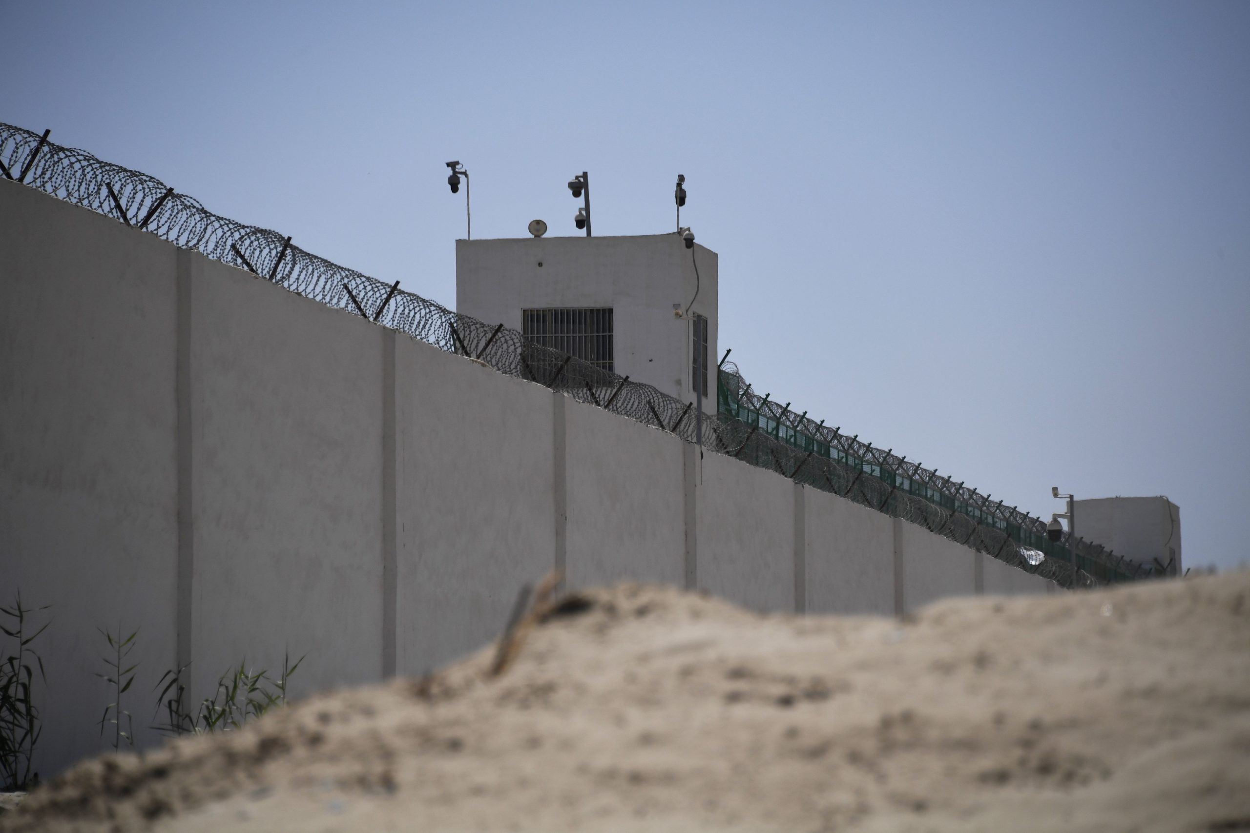 "This photo taken on May 31, 2019 shows the outer wall of a complex which includes what is believed to be a re-education camp where mostly Muslim ethnic minorities are detained, on the outskirts of Hotan, in China's northwestern Xinjiang region. - As many as one million ethnic Uighurs and other mostly Muslim minorities are believed to be held in a network of internment camps in Xinjiang, but China has not given any figures and describes the facilities as ""vocational education centres"" aimed at steering people away from extremism. (Photo by Greg Baker/AFP via Getty Images)"