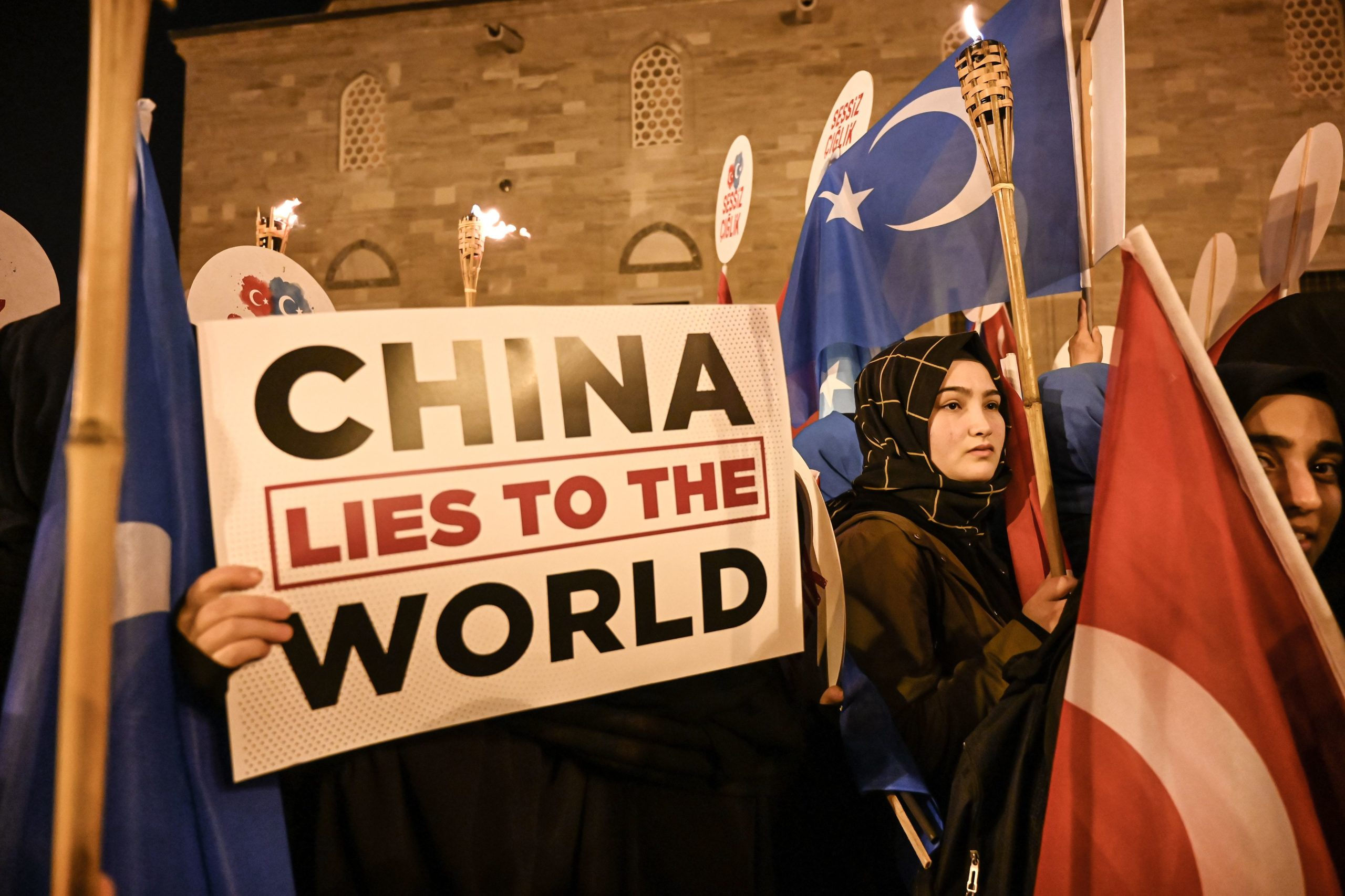 Supporters of China's Muslim Uighur minority wave flag of East Turkestan and hold placards on December 20, 2019 during a demostration at Fatih in Istanbul. - More than 1,000 protesters marched on December 20, 2019, in Istanbul to protest against China over its treatment of mainly Muslim Uighurs in Xinjiang, an AFP correspondent said. They called for an end to the crackdown in China's northwestern region, where upwards of one million Uighurs and other mostly Muslim minorities are believed to be held in re-education camps. (Photo by Ozan KOSE / AFP) (Photo by OZAN KOSE/AFP via Getty Images)