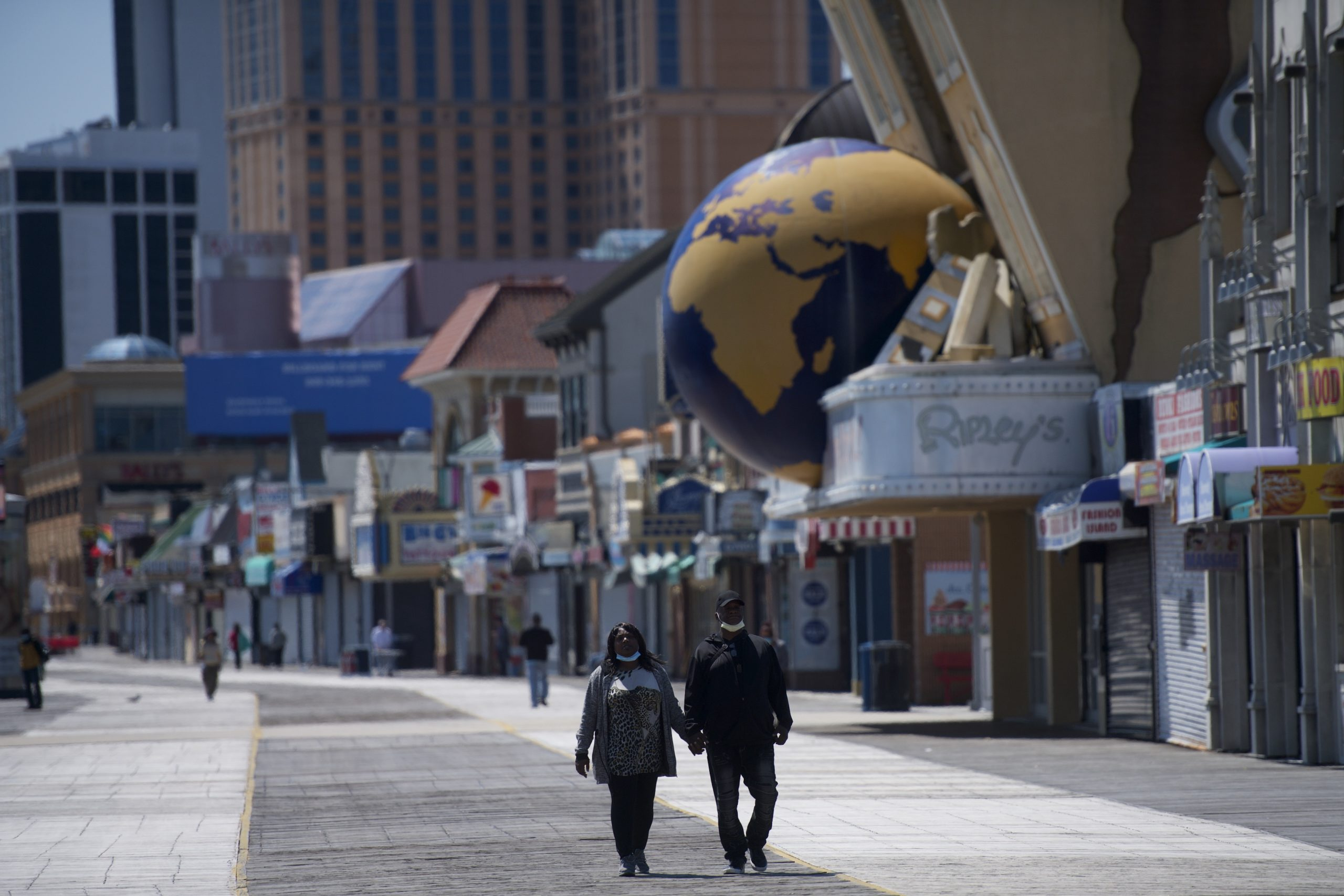 A couple walks on the boardwalk past shuttered stores during the coronavirus pandemic on May 7, 2020 in Atlantic City, New Jersey. (Mark Makela/Getty Images)
