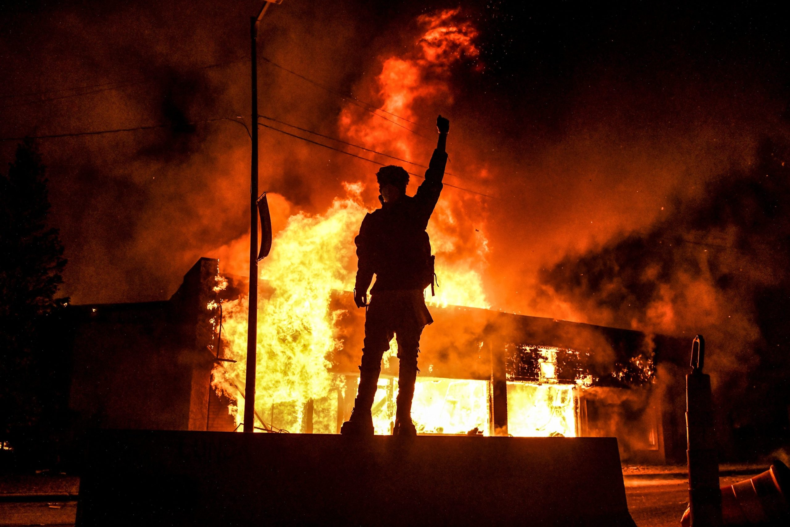 TOPSHOT - A protester reacts standing in front of a burning building set on fire during a demonstration in Minneapolis, Minnesota, on May 29, 2020, over the death of George Floyd, a black man who died after a white policeman kneeled on his neck for several minutes. - Violent protests erupted across the United States late on May 29 over the death of a handcuffed black man in police custody, with murder charges laid against the arresting Minneapolis officer failing to quell seething anger. (Photo by Chandan KHANNA / AFP) (Photo by CHANDAN KHANNA/AFP via Getty Images)
