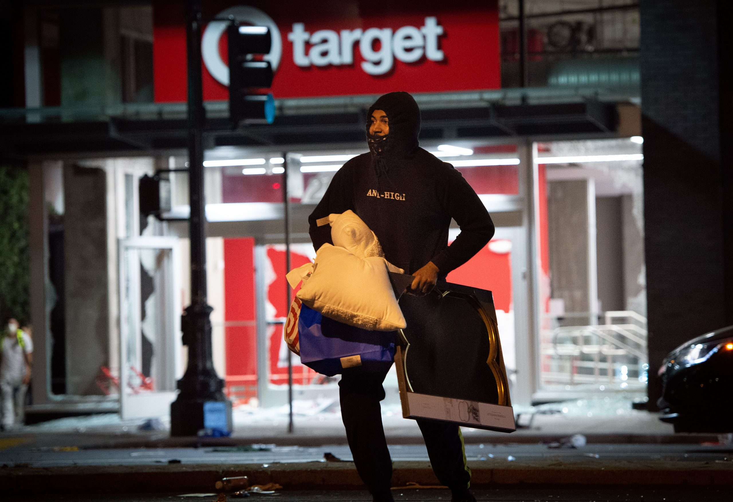 A looter rob a Target store as protesters face off against police in Oakland California on May 30, 2020, over the death of George Floyd, a black man who died after a white policeman kneeled on his neck for several minutes. - Violent protests erupted across the United States late on May 29 over the death of a handcuffed black man in police custody, with murder charges laid against the arresting Minneapolis officer failing to quell boiling anger (JOSH EDELSON/AFP via Getty Images)